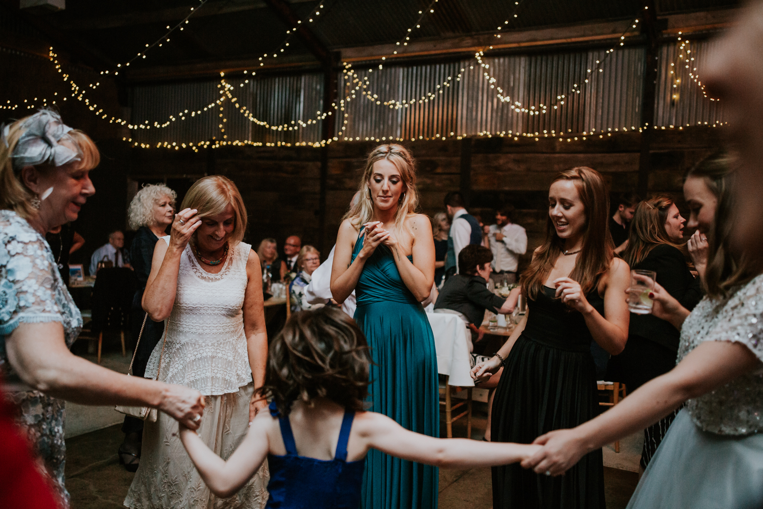 Bridesmaid is dancing with other guests at Harelaw farm DIY wedding in Ayrshire.
