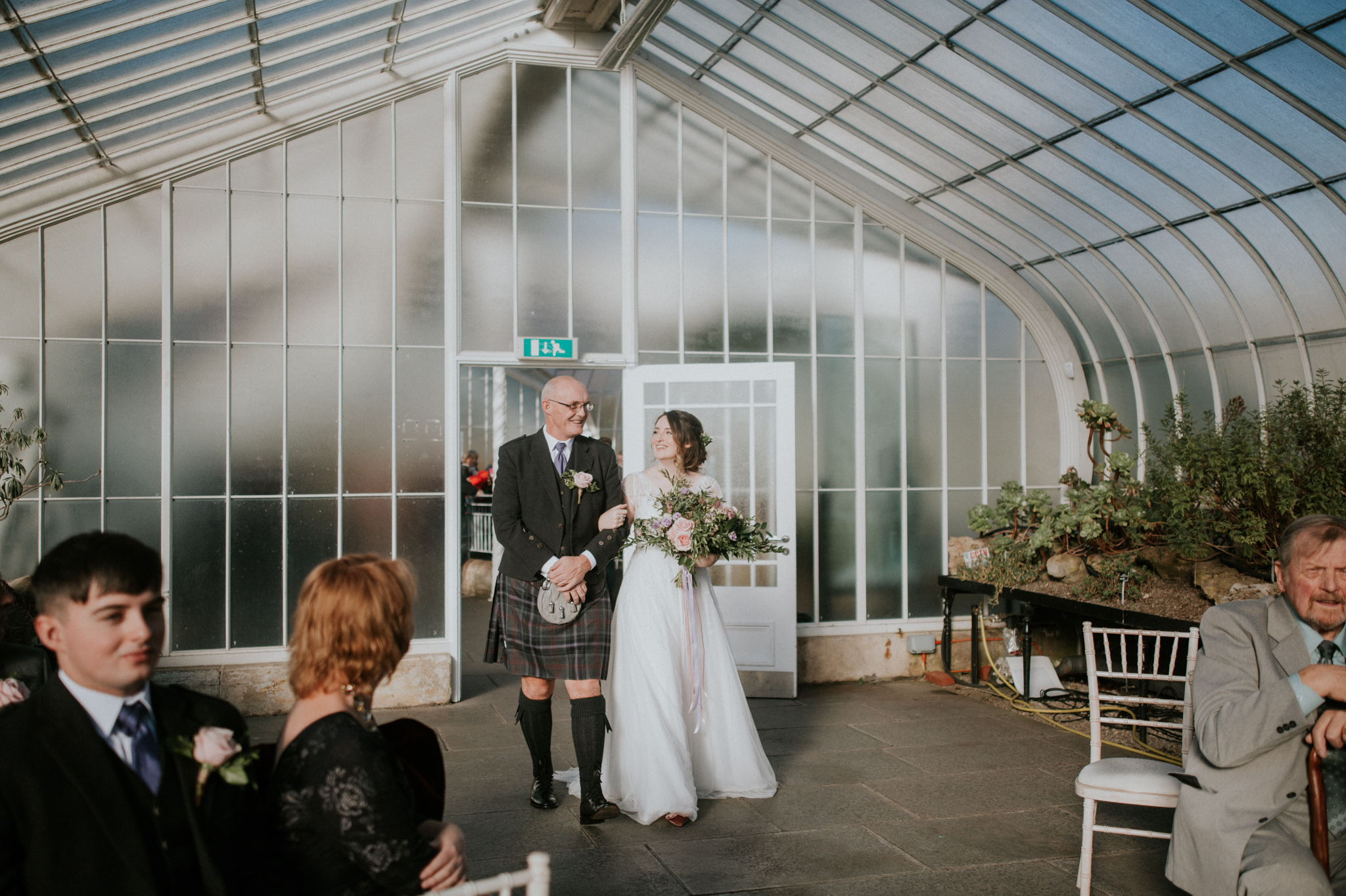 The bride is walking at the aisle with her father at the Botanic Gardens in Glasgow