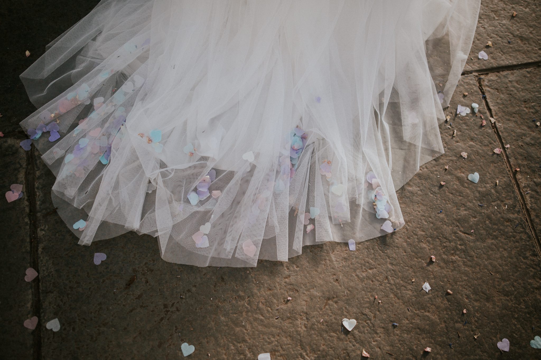 Confetti petals on the wedding dress