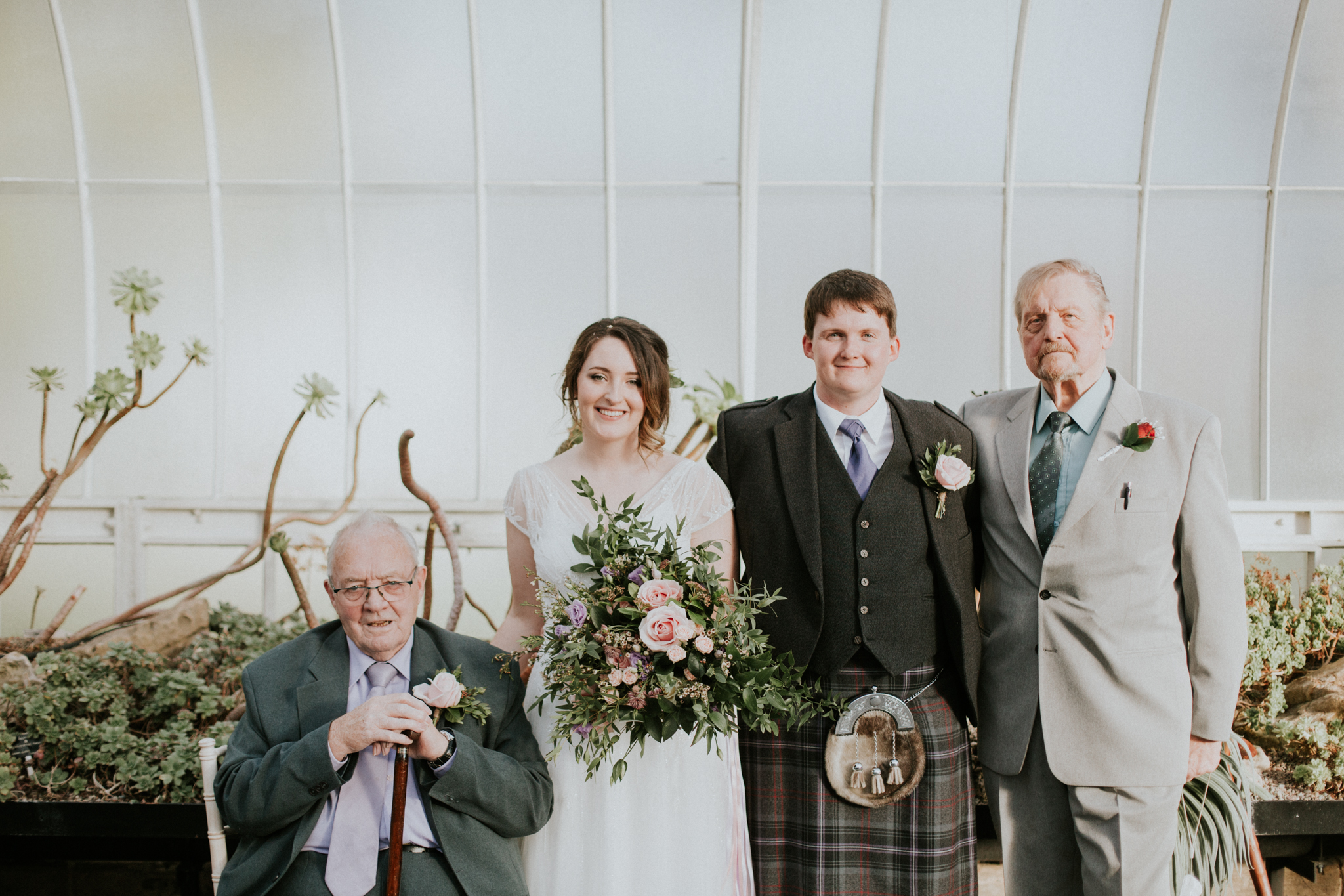 A family portrait of the bride and groom with their grand fathers
