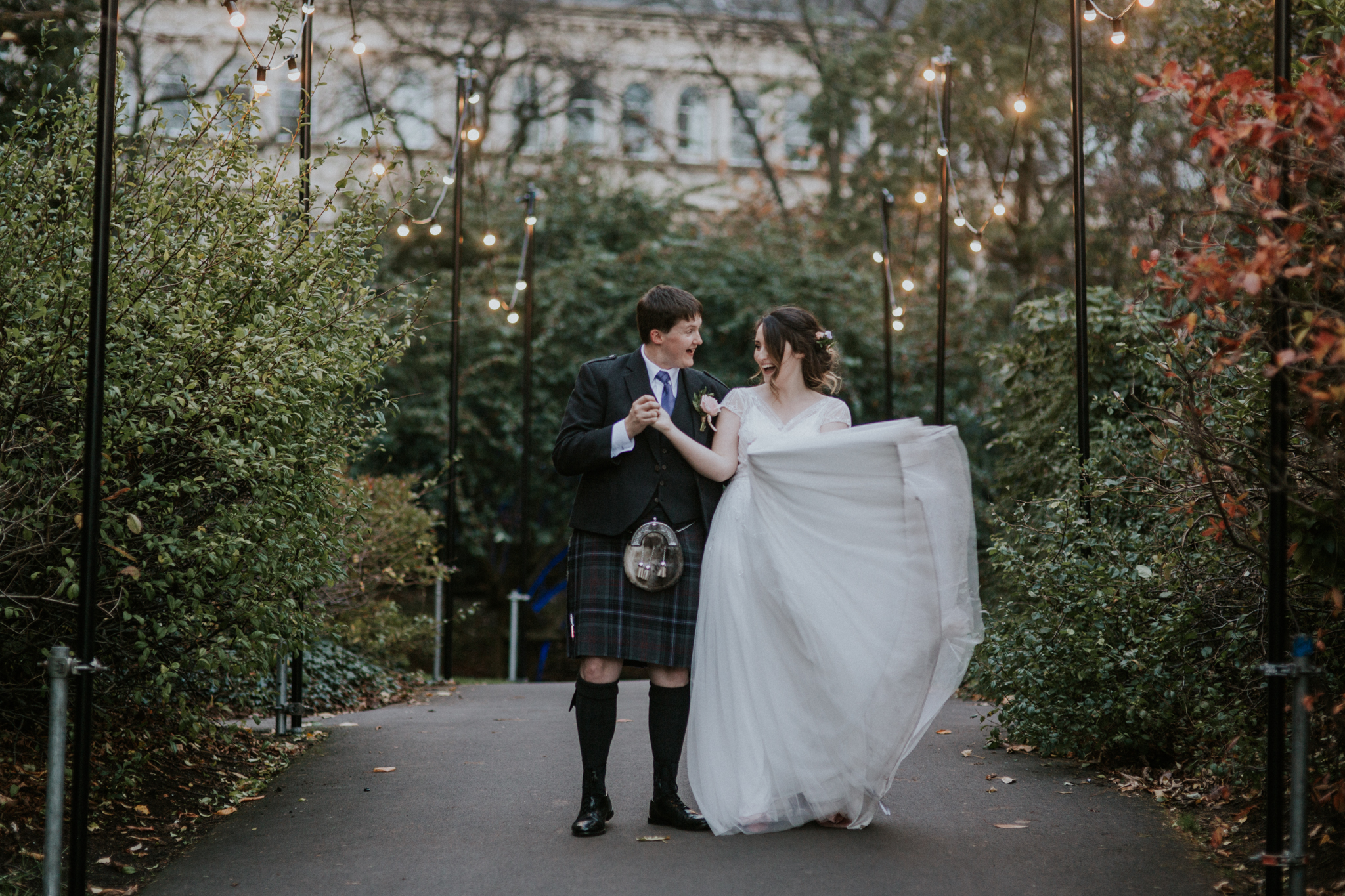 Bride and groom are dancing under the fairy lights in Glasgow Botanic Gardens