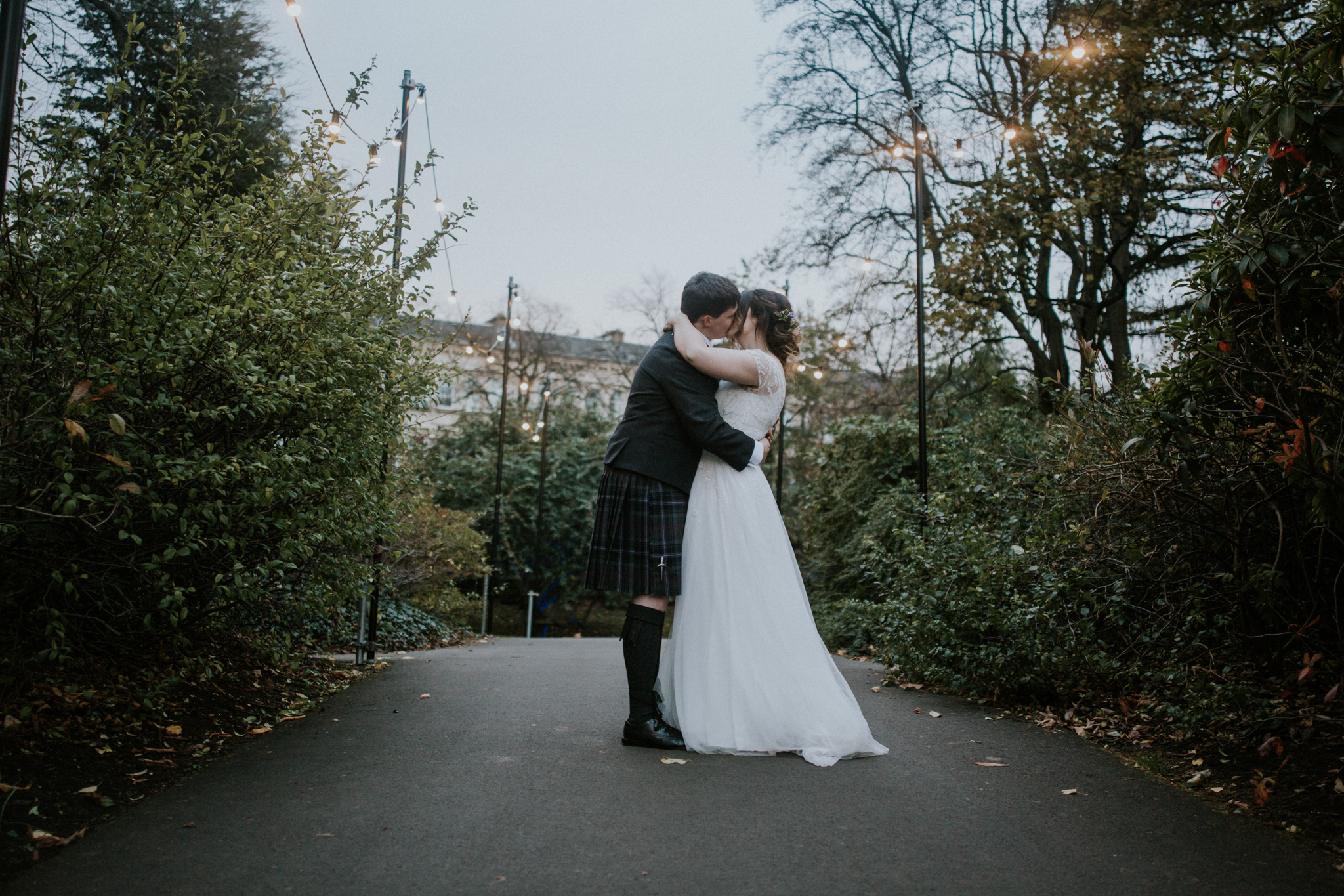 Groom is kissing the bride under the fairy light in Glasgow at the Botanic Gardens