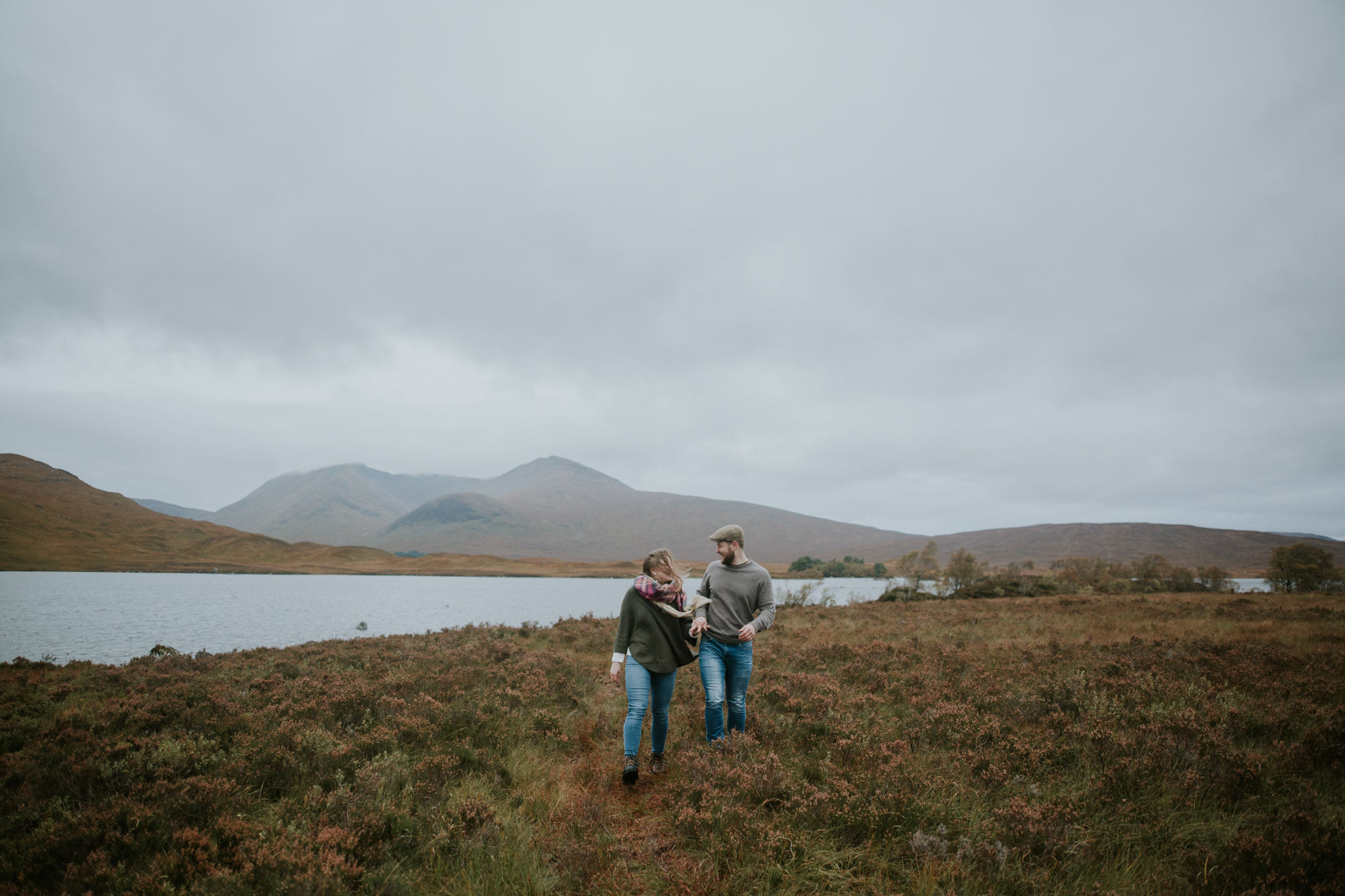 The couple walk in the moody and windy Scottish Glencoe