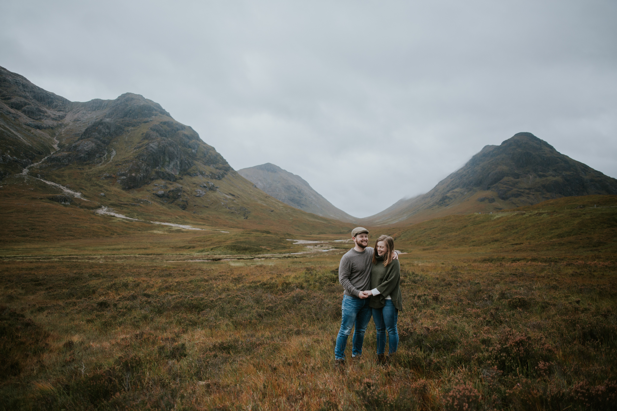 The couple is standing at the breathtaking view of the spectacular Glencoe in the Scottish Highlands