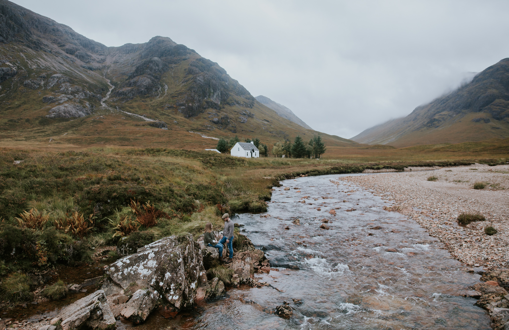The couple is sitting on the rocks in the middle of the Scottish Glencoe