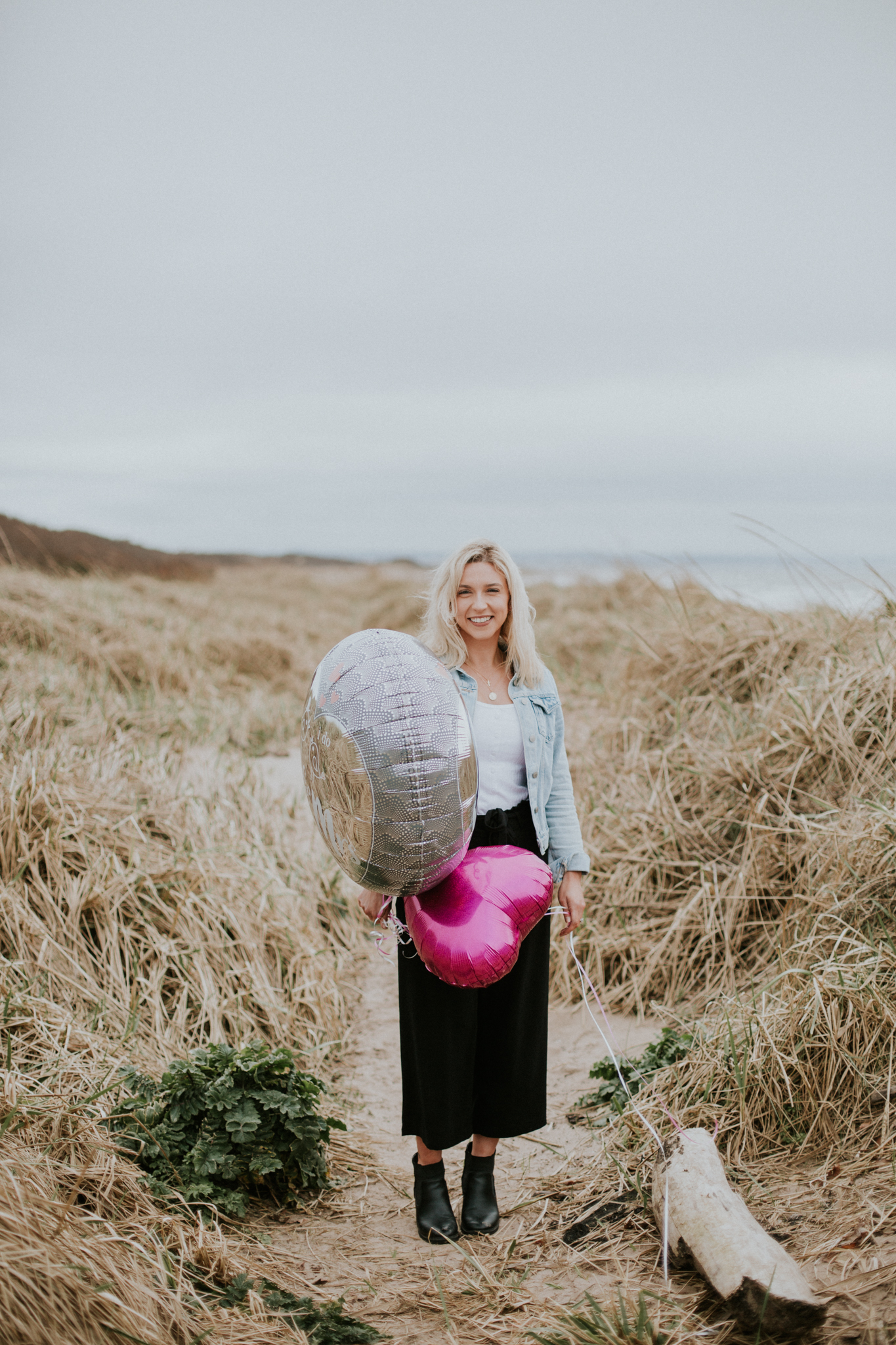 The bride is standing on the beach in Troon and holding the balloons