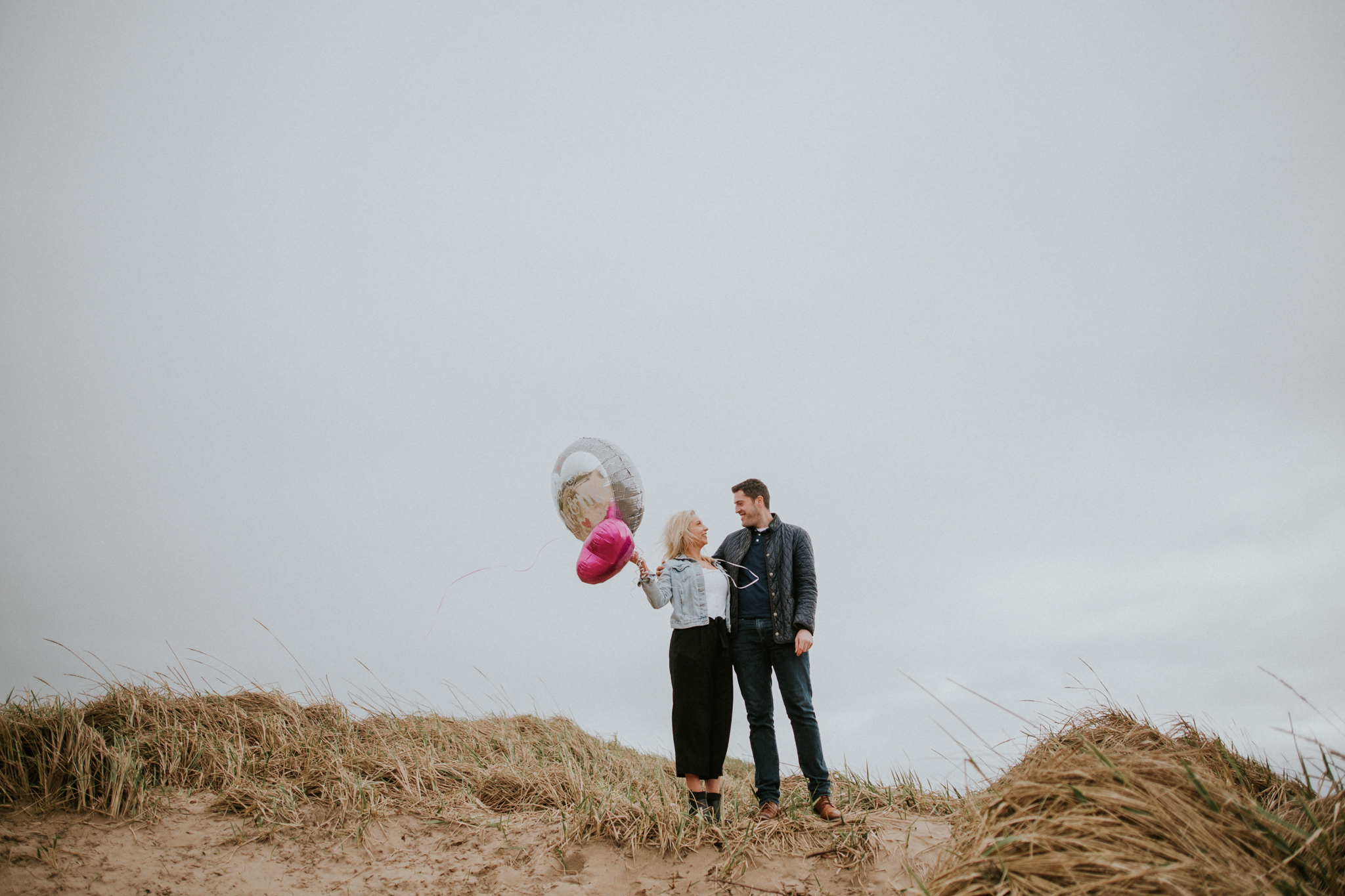 The couple is standing on the beach with the balloons