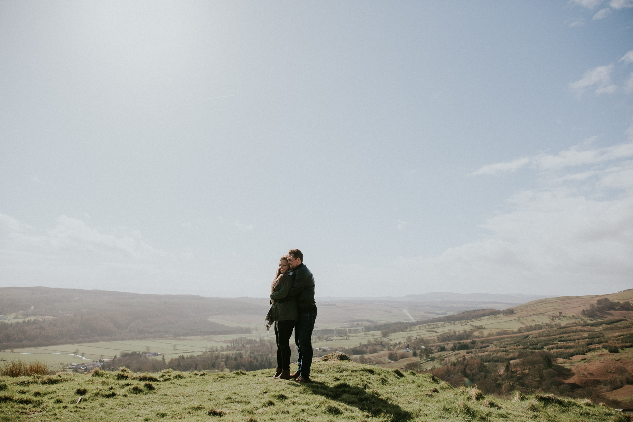 The couple is standing and holding each other on the top of the Campsie Fells, Scotland wedding photographer