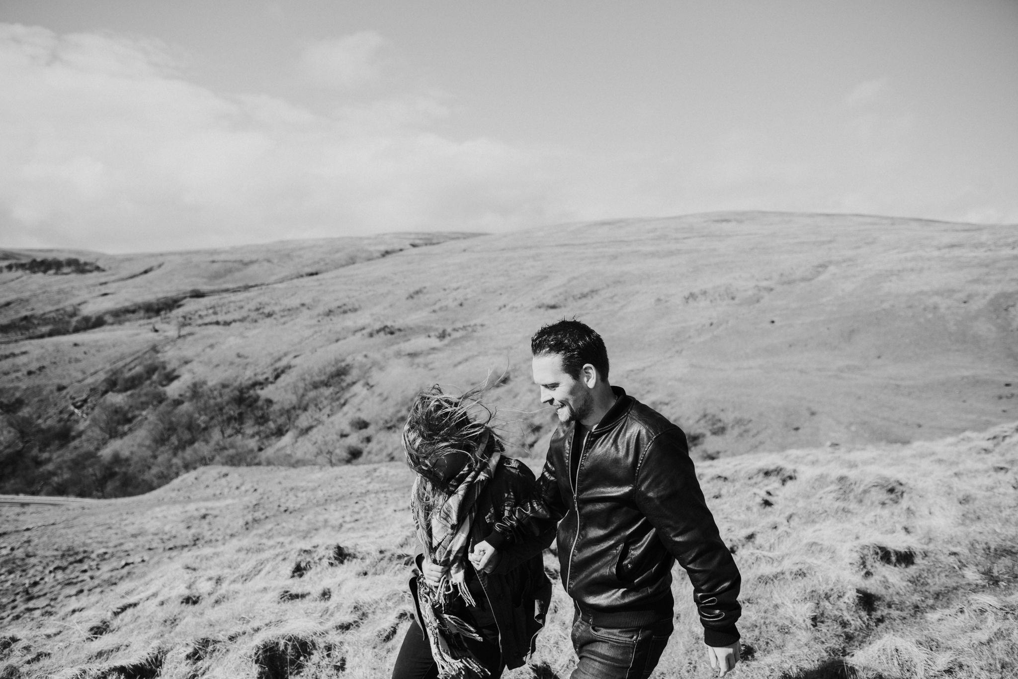 The happy couple is walking together on the top of the hills in Scotland
