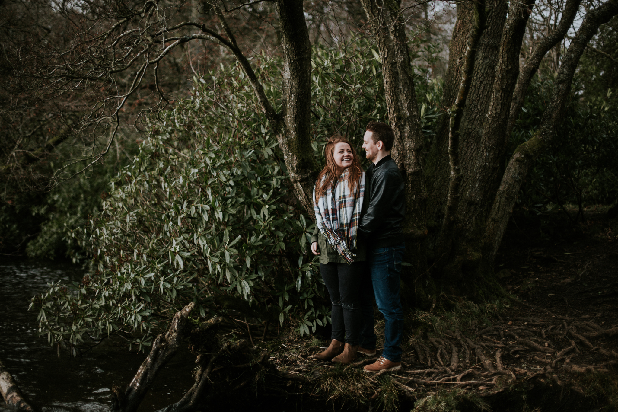 The future bride and groom are standing on the edge of the lake at the wild Mugdock Country Park