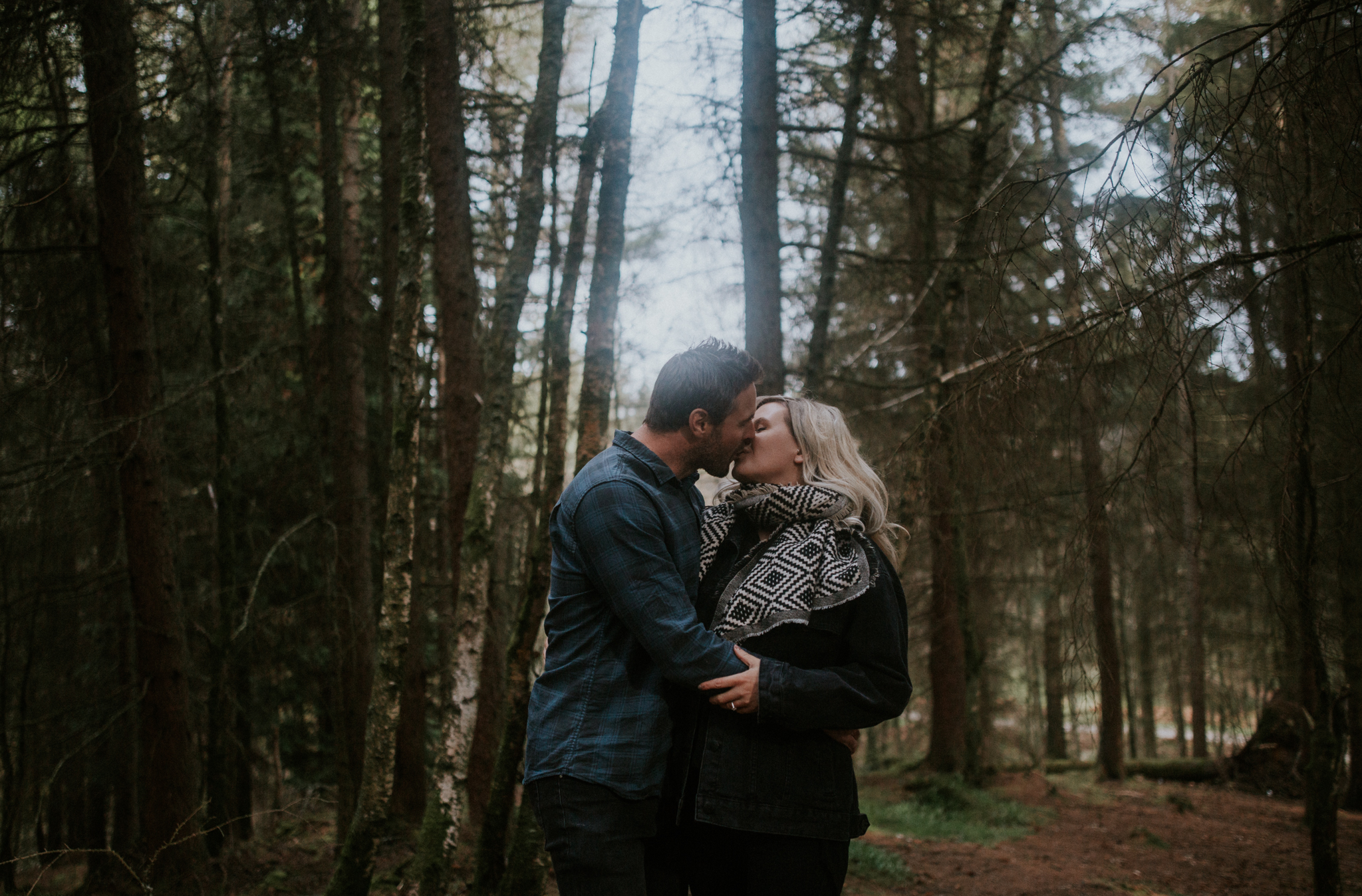 The newly engaged couple is kissing in the Balmaha forest, Loch Lomond wedding and engagement photographer
