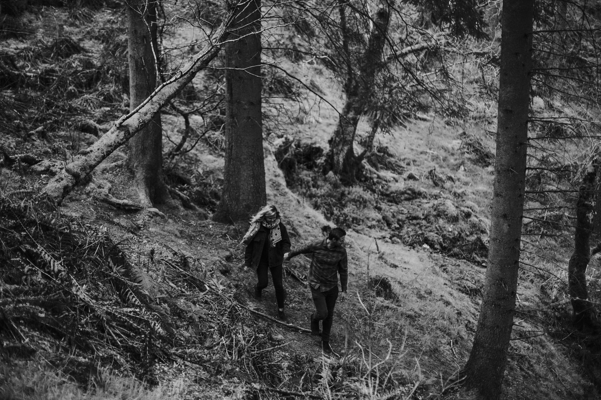 The adventurous newly engaged couple is exploring the Balmaha forest in Loch Lomond area