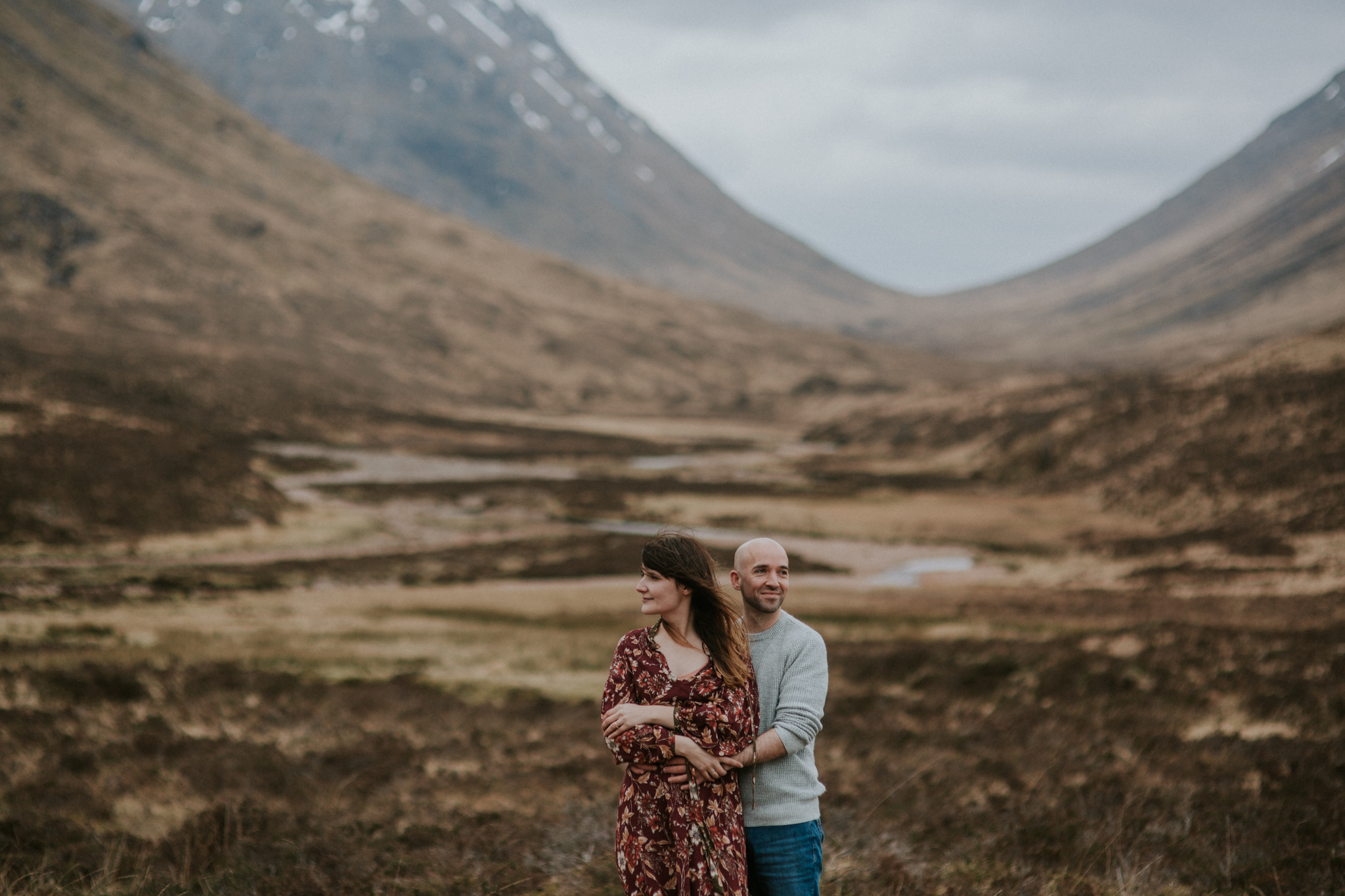 The engaged couple is cuddle each other in the breathtaking Glencoe Scottish Highlands