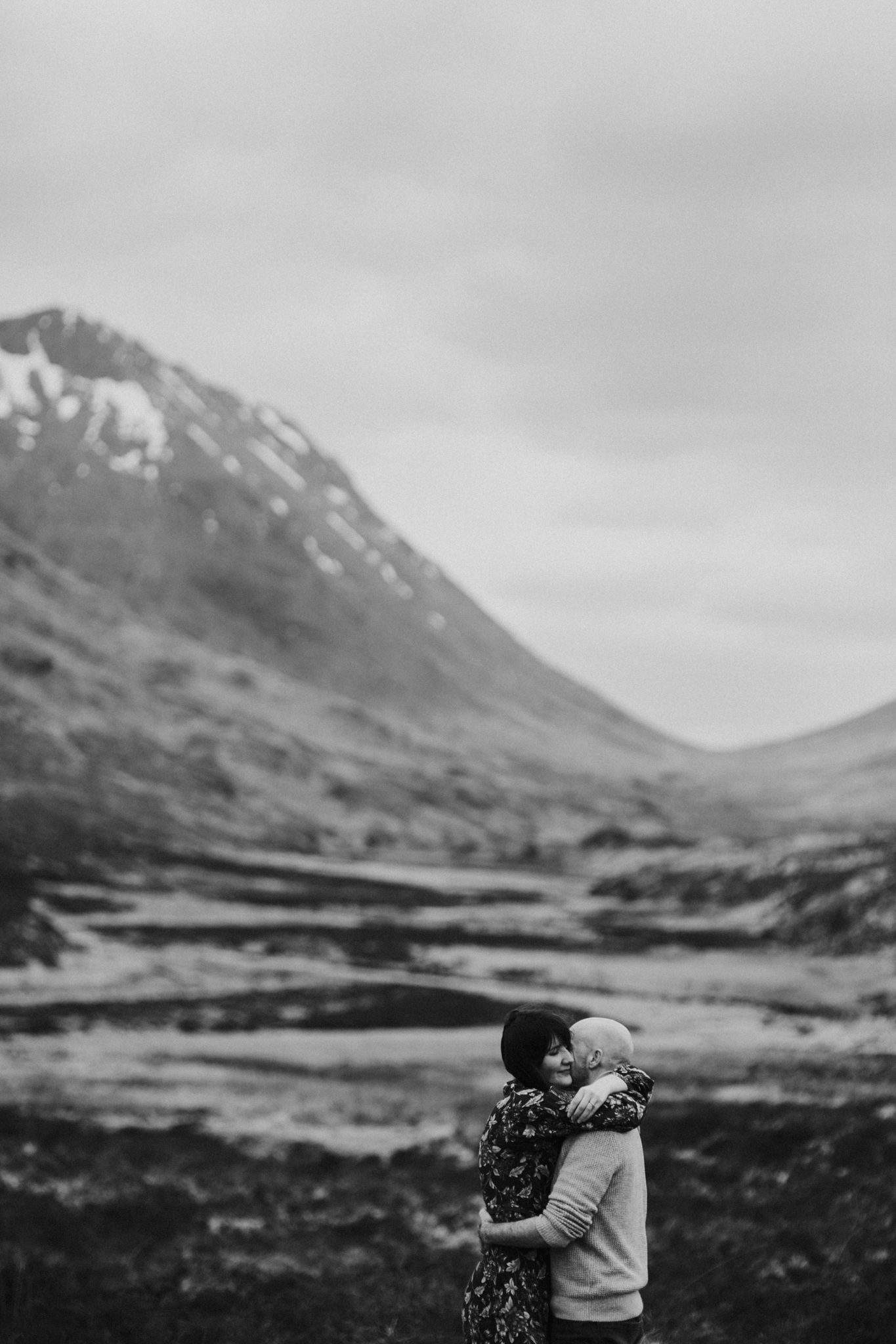 The portrait of the bride and groom cuddling on the background of Scottish Glencoe