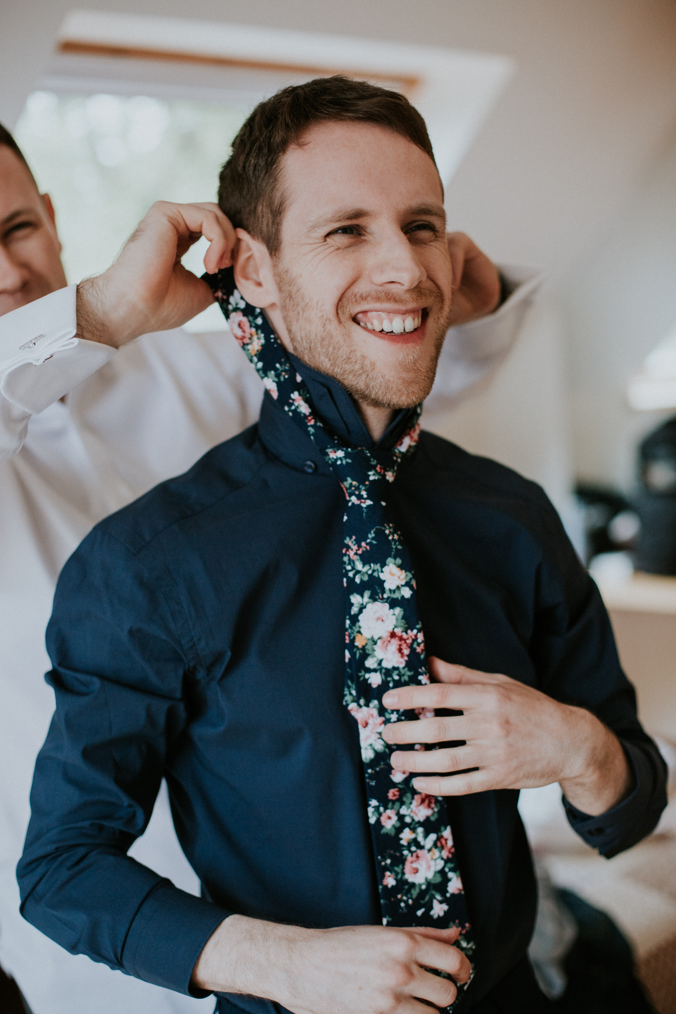 The groom is getting ready and wearing the colourful, alternative tie
