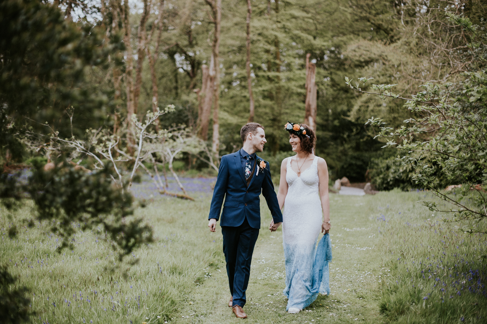 The bride and groom are walking together in the woodland of Inish Beg Estate in Ireland
