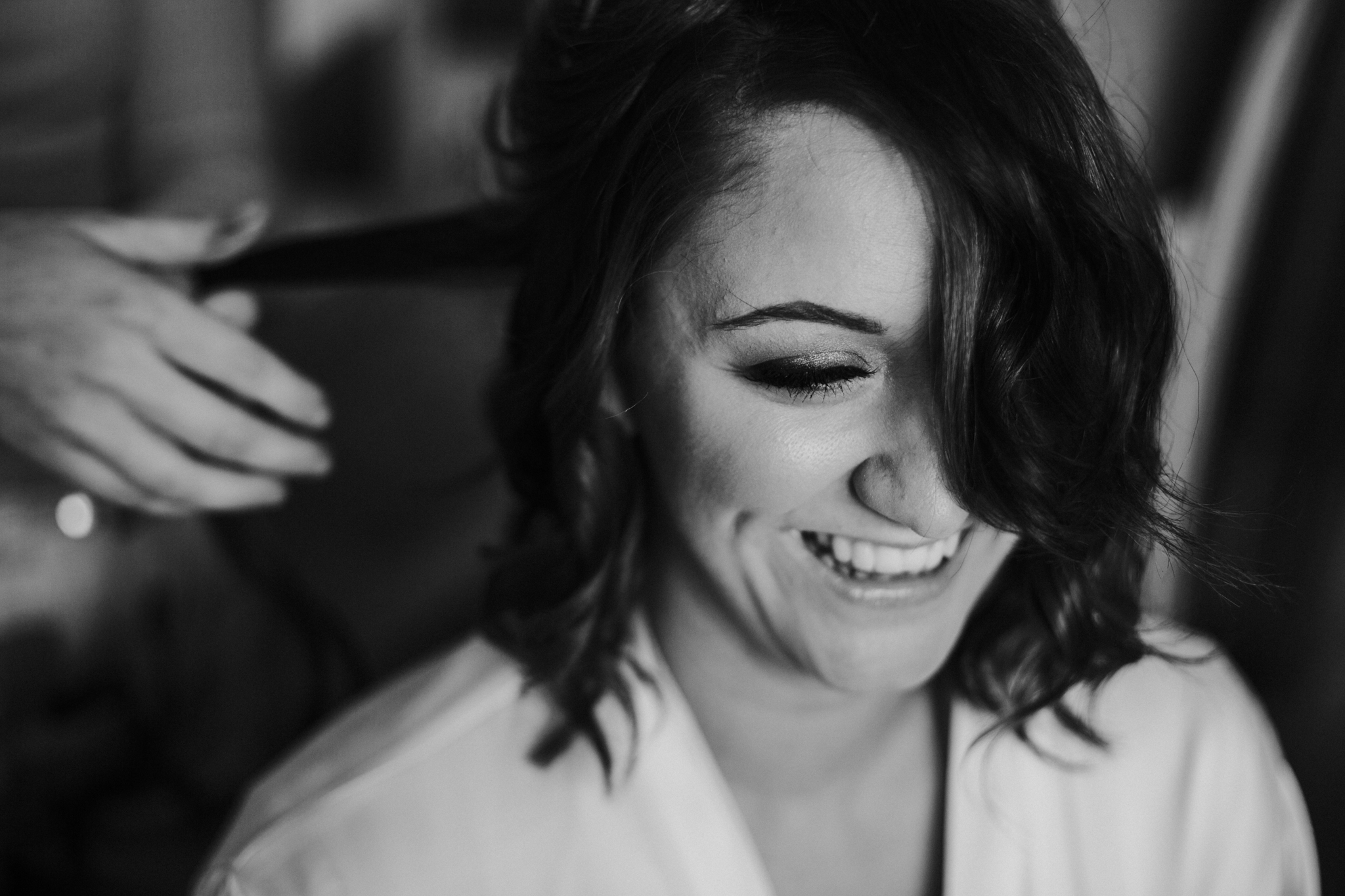 The bride is laughing during her hair styling at the Harelaw farm in Ayrshire