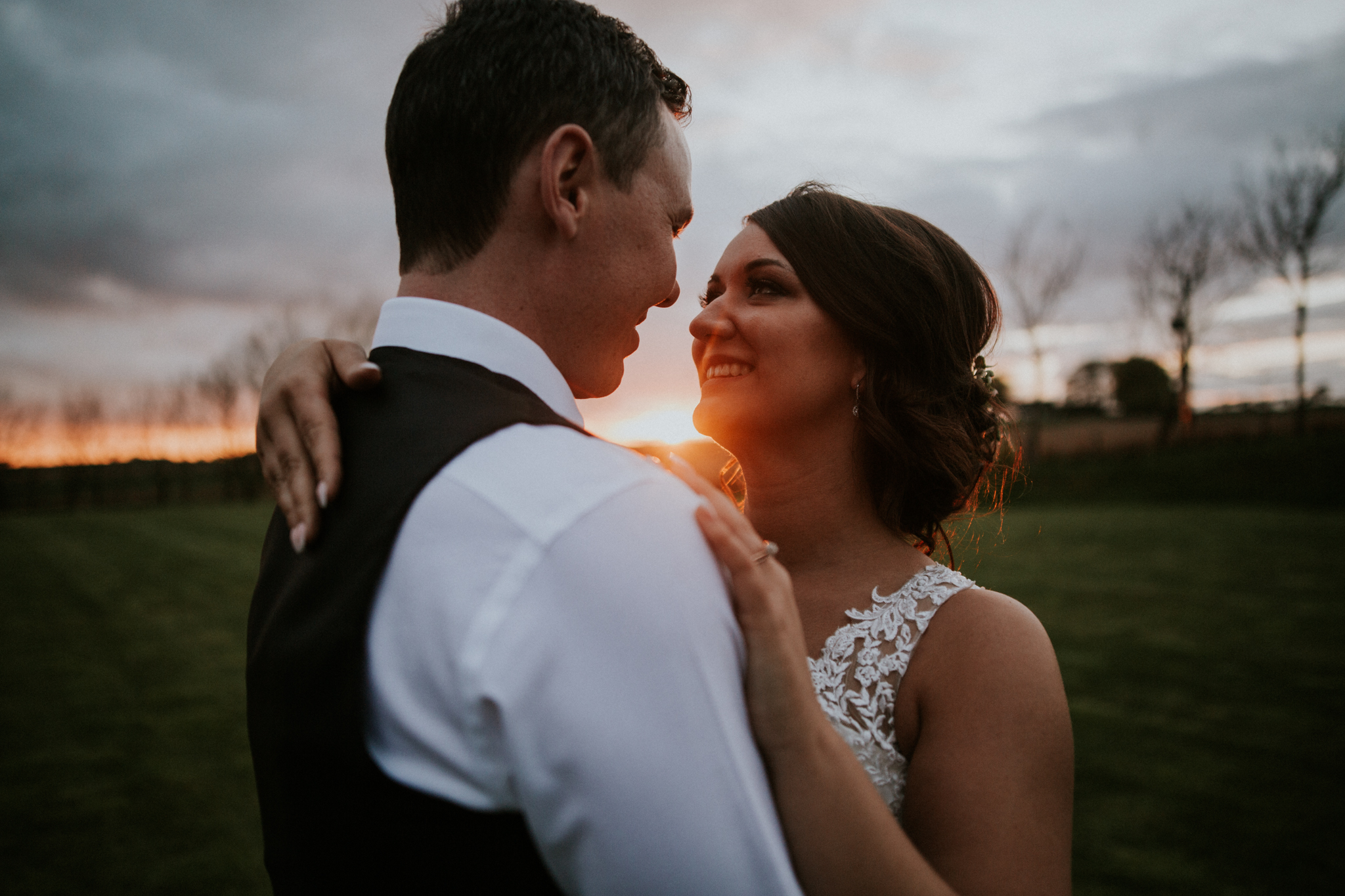 A golden sunset photo of the newlyweds on the field of the Harelaw farm