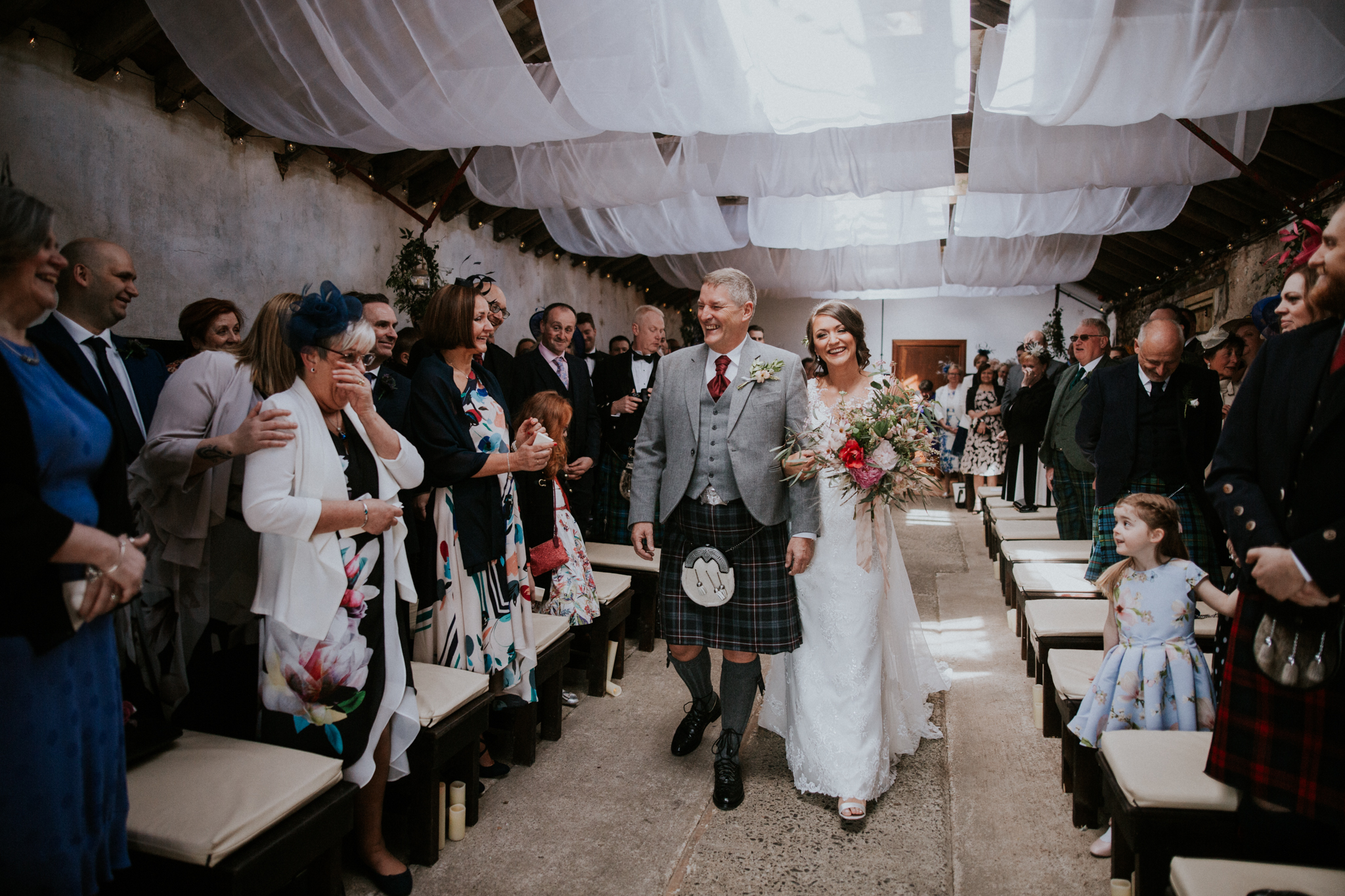 The bride is walking together with her father into the ceremony room at the Harelaw farm