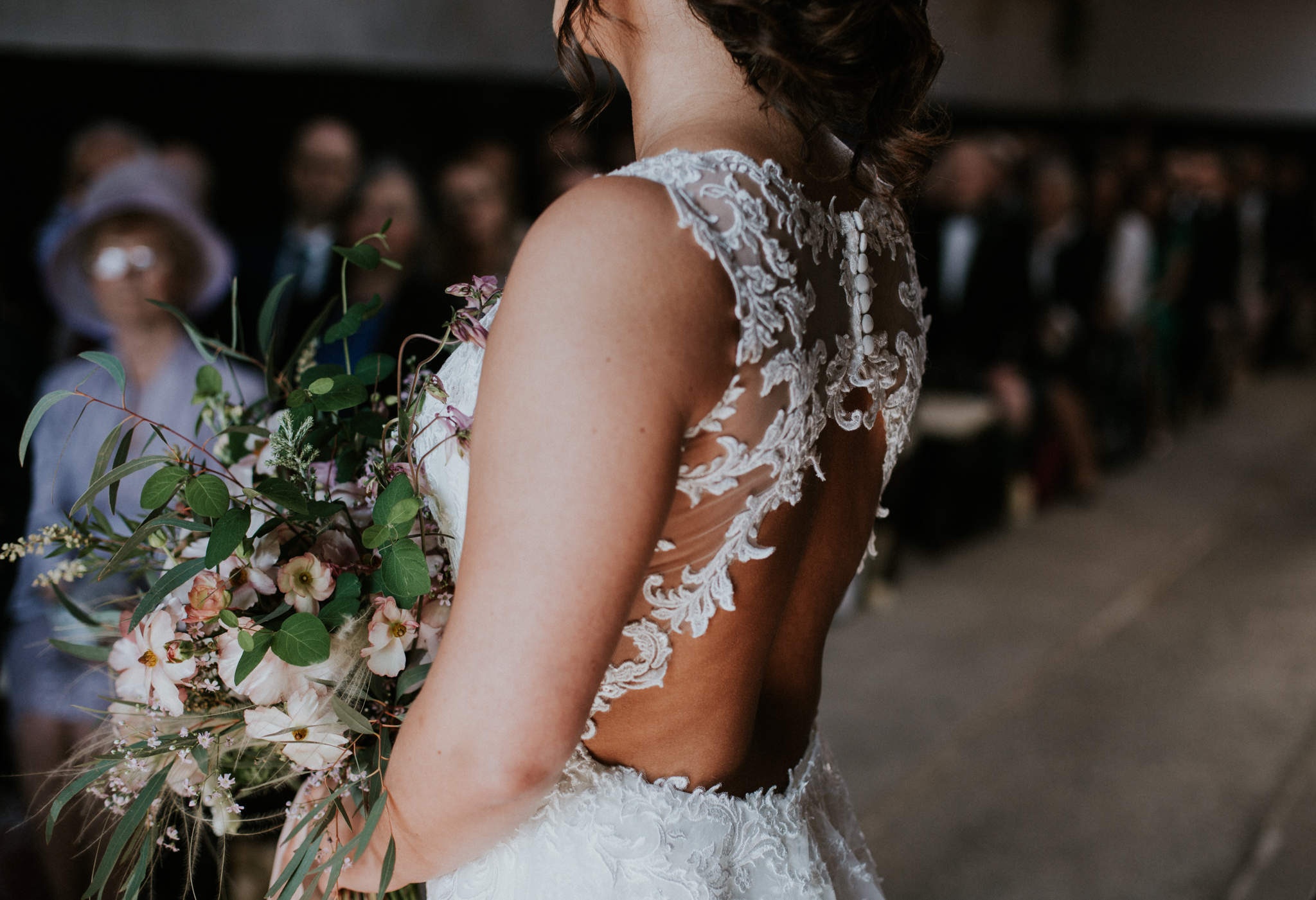 The close up shot of the bride's wedding dress at the ceremony in Scotland