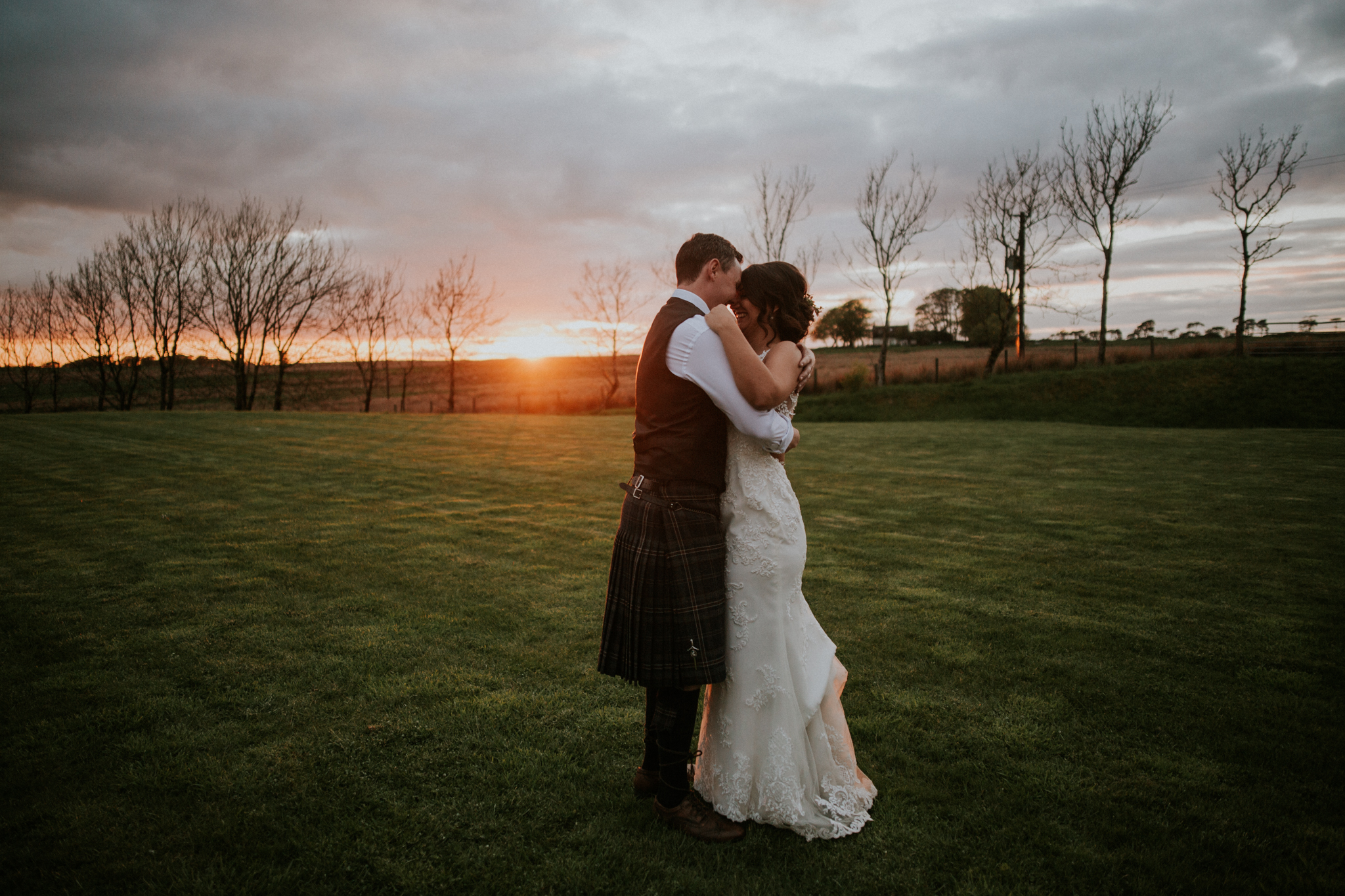 The couple is cuddle during the golden sunset photo shoot at the Harelaw farm