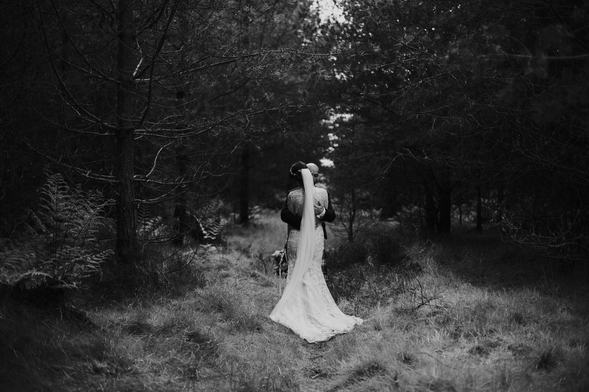 The creative and intimate shot of the newlyweds in the wild forest