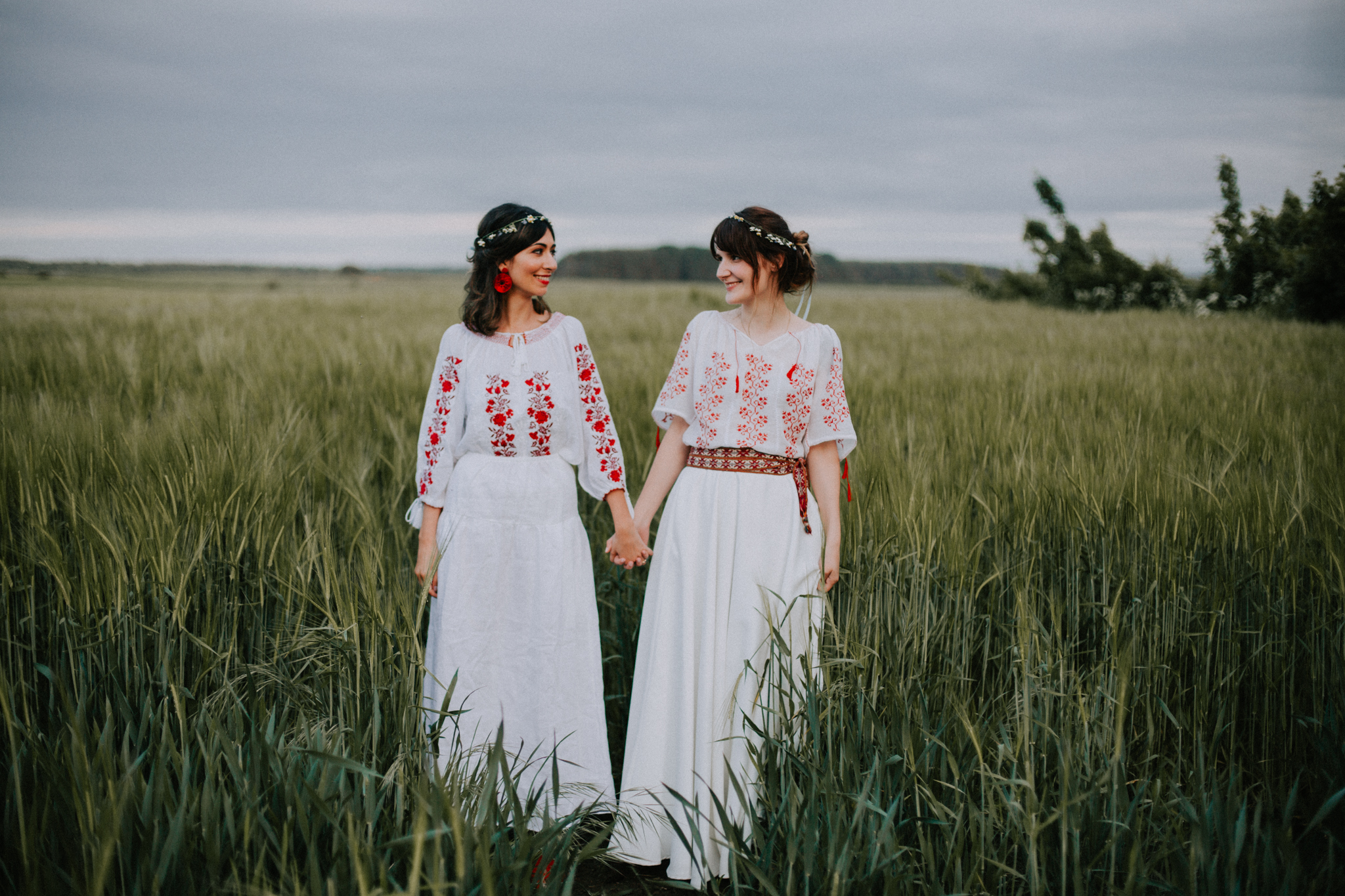 The bride and the maid of honour in the field in a Romanian traditional outfit
