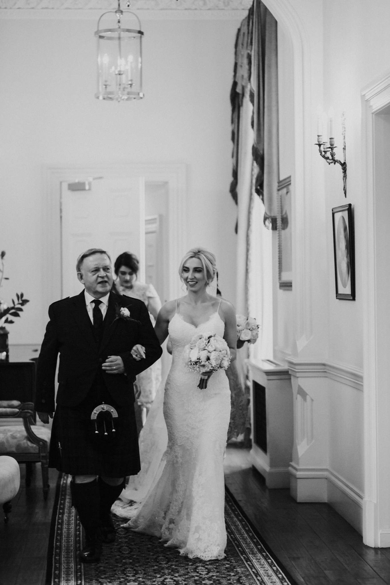 The bride is walking with her father to the ceremony room at the Crossbasket castle