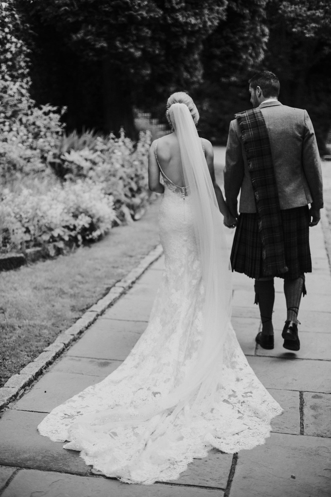 The bride and the groom are walking together on the ground of Crossbasket castle