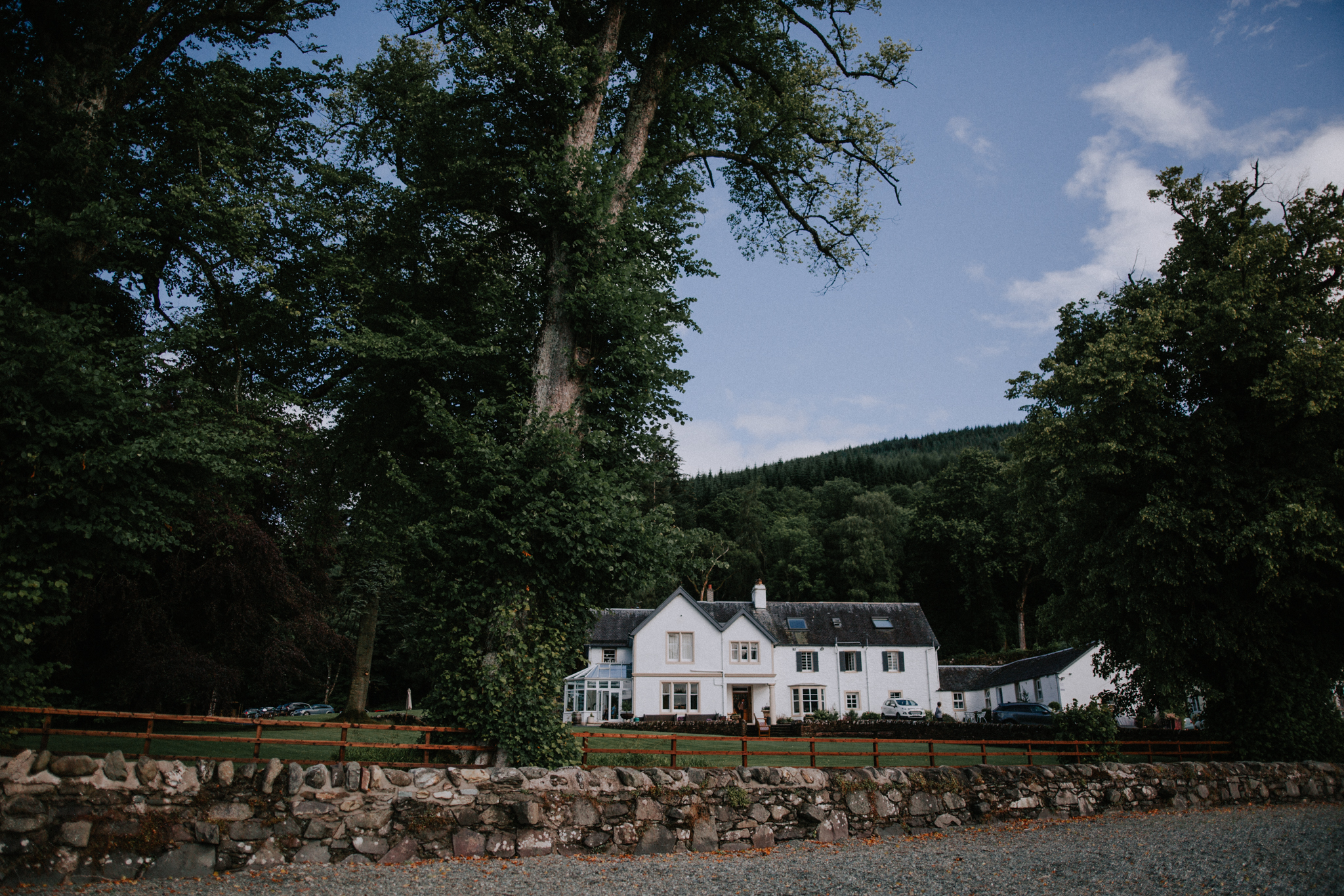 A wide angle landscape photo of the Altskeith Country House on Loch Are