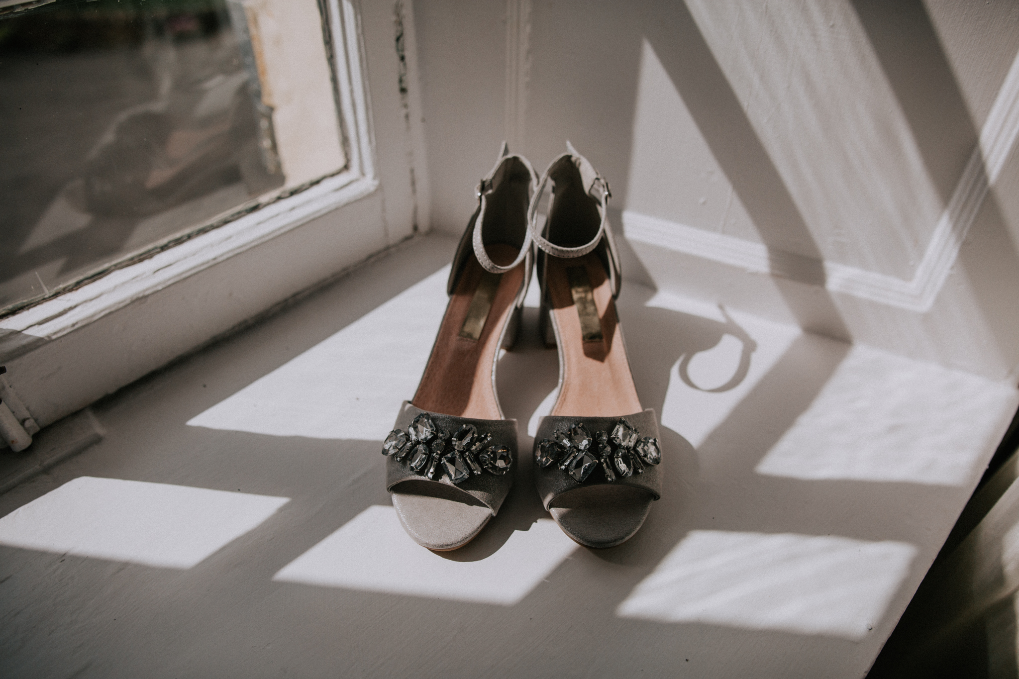 The bride's shoes on the white window sill at the Altskeith Country House on Loch Ard