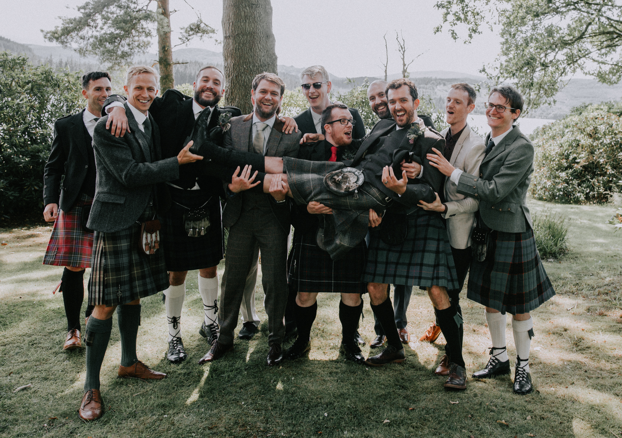 A bunch of groomsmen holding the groom on arms and laughing