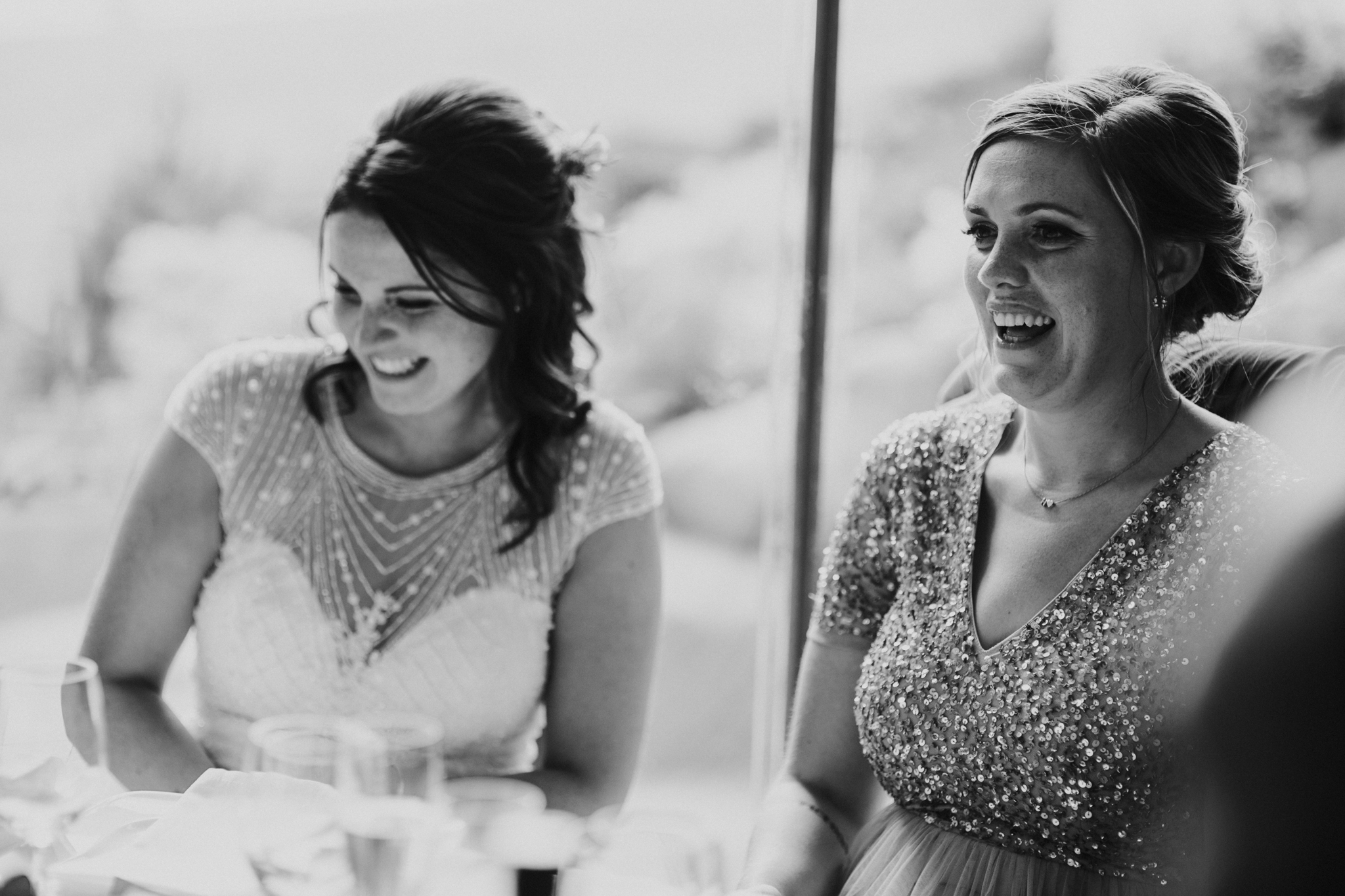 The sister of the bride is laughing during the speeches