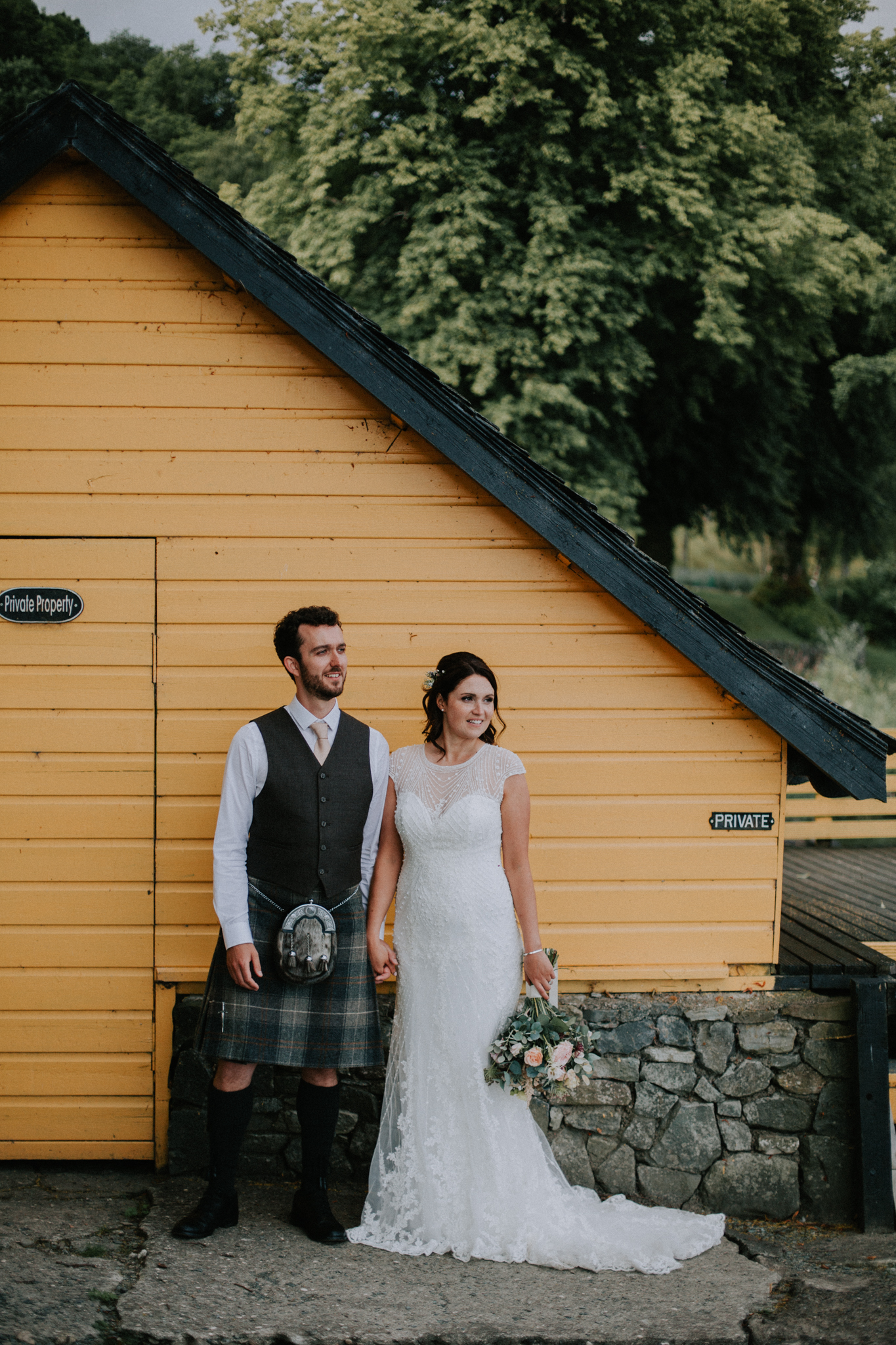 The couple is standing next to the yellow boat house during the evening couple shoot at Altskeith Country House