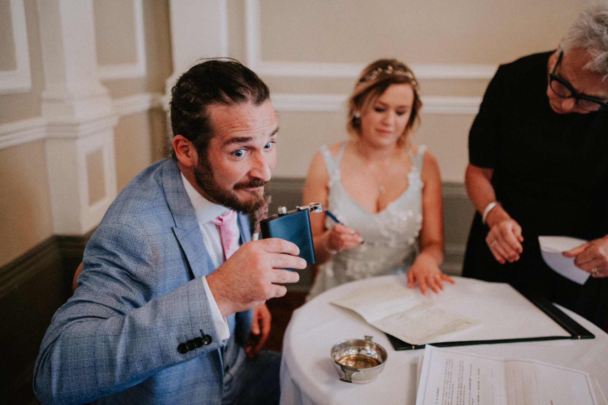 The groom is sipping whisky during the signing register