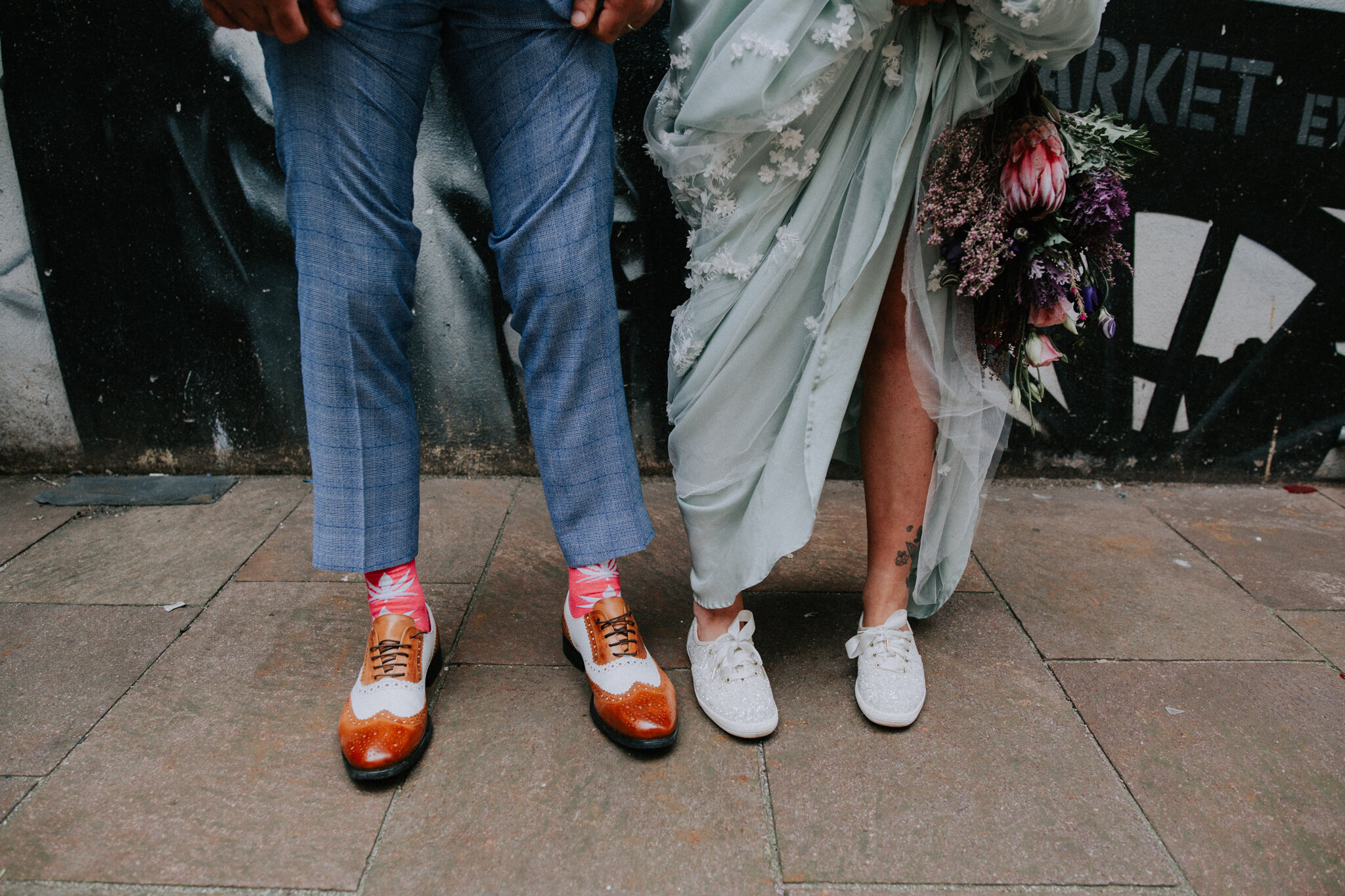 Close up shot of the alternative wedding groom's shoes and bride's keds