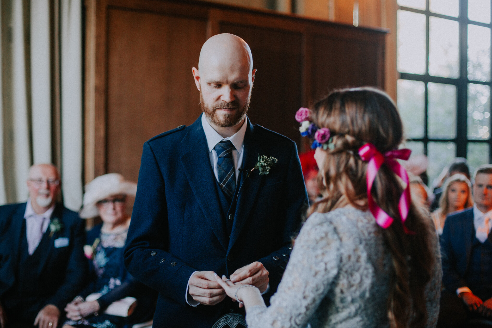 The groom is putting the wedding ring on the bride's finger