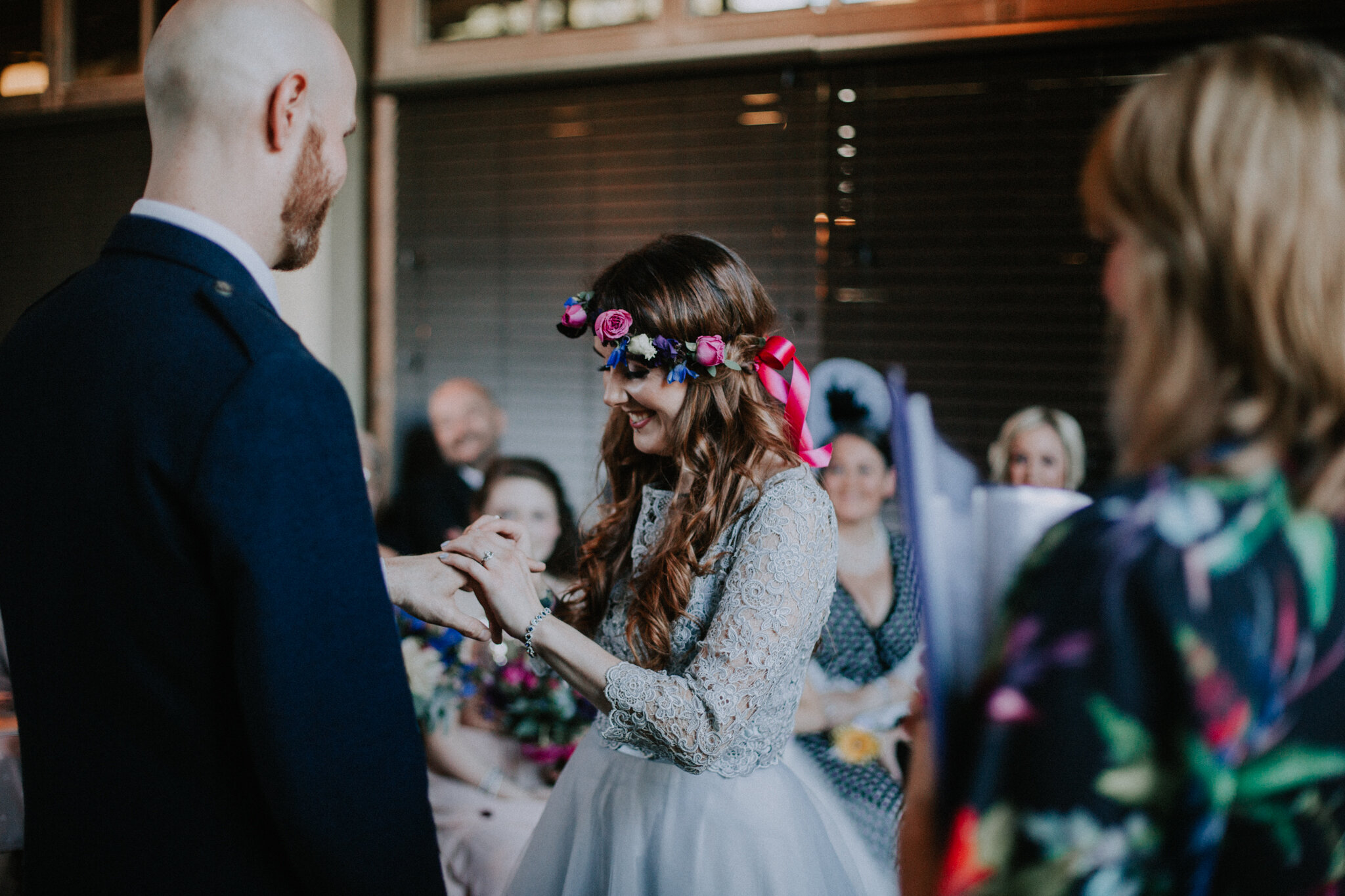 The bride is putting the wedding ring on groom's finger