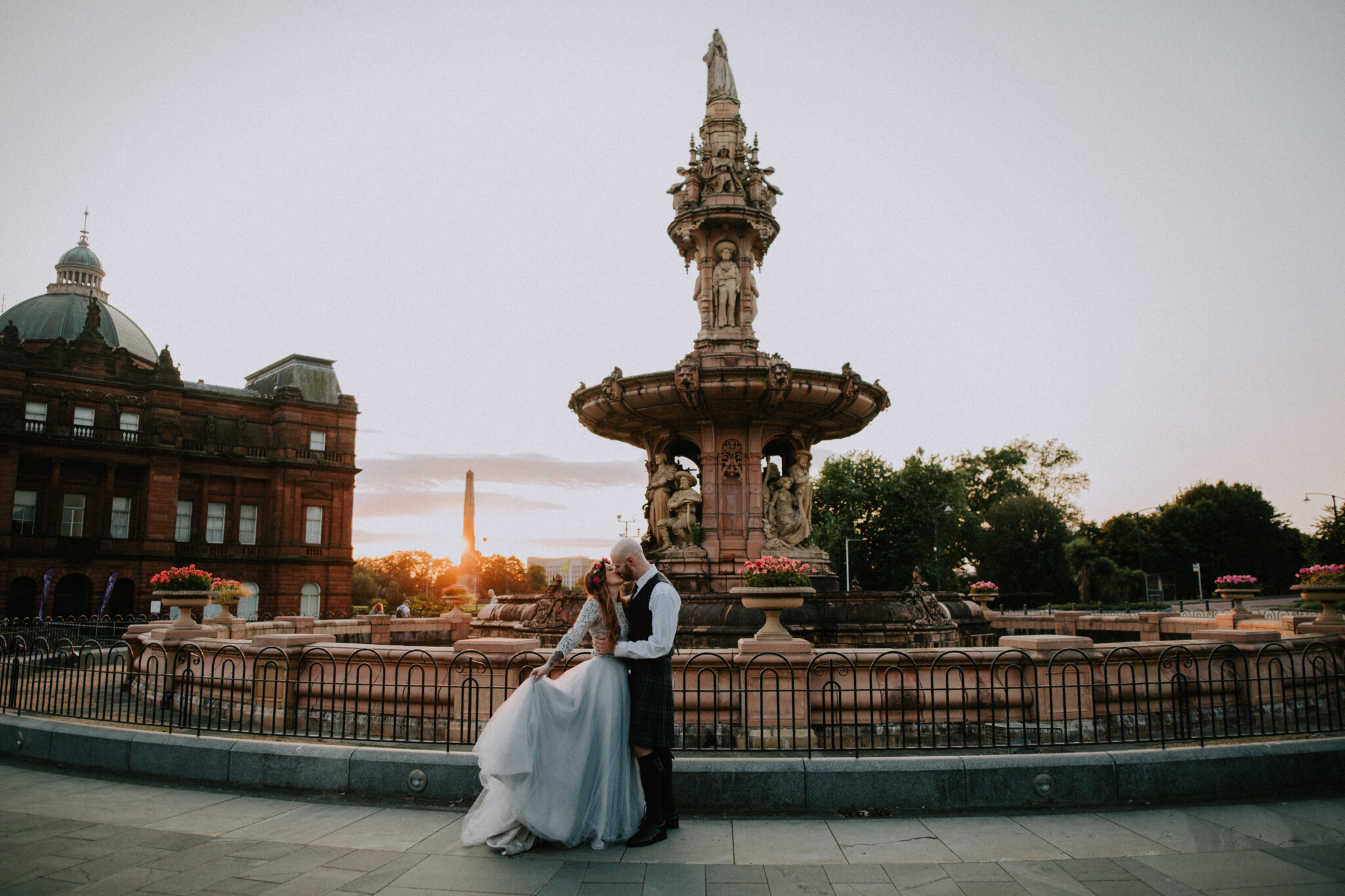 A romantic and epic couple portrait shot during the golden sunset at the fountain in Glasgow Green