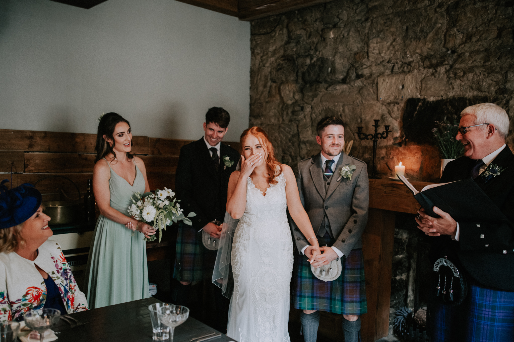 The bride is laughing during the wedding ceremony at the Bothy