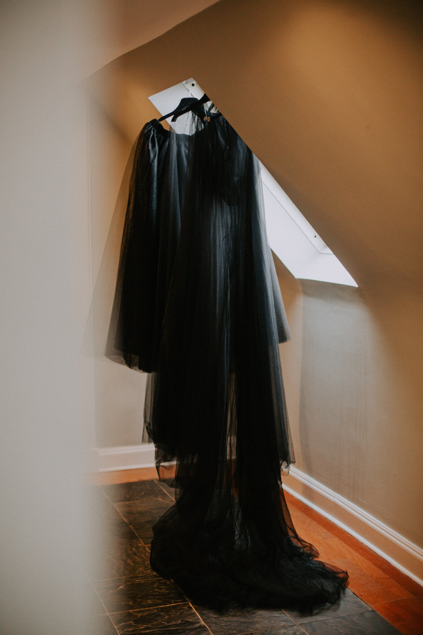 Halloween wedding outfit is hanging next to the window