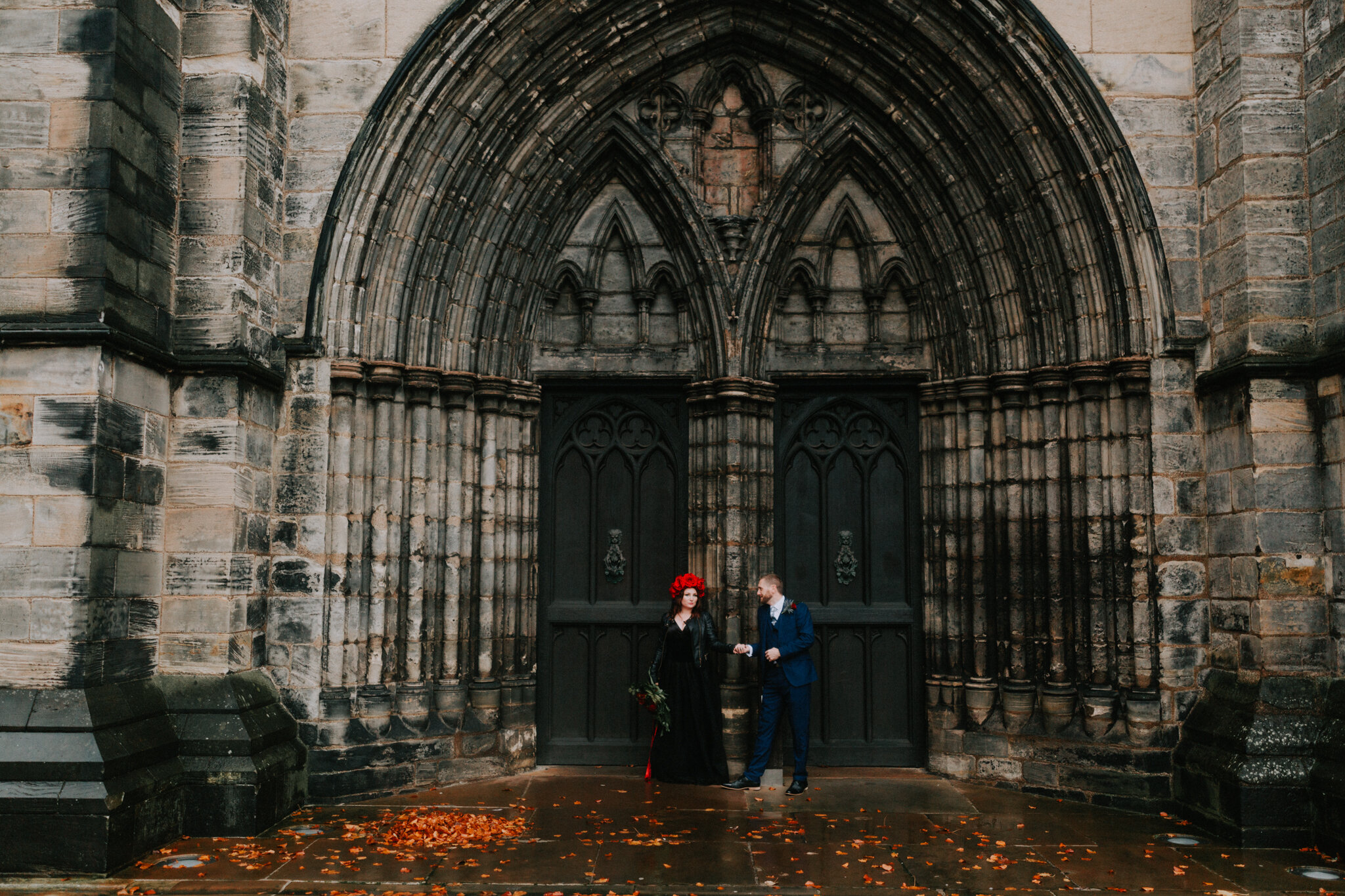 The couple is posing next to the Cathedral black doors
