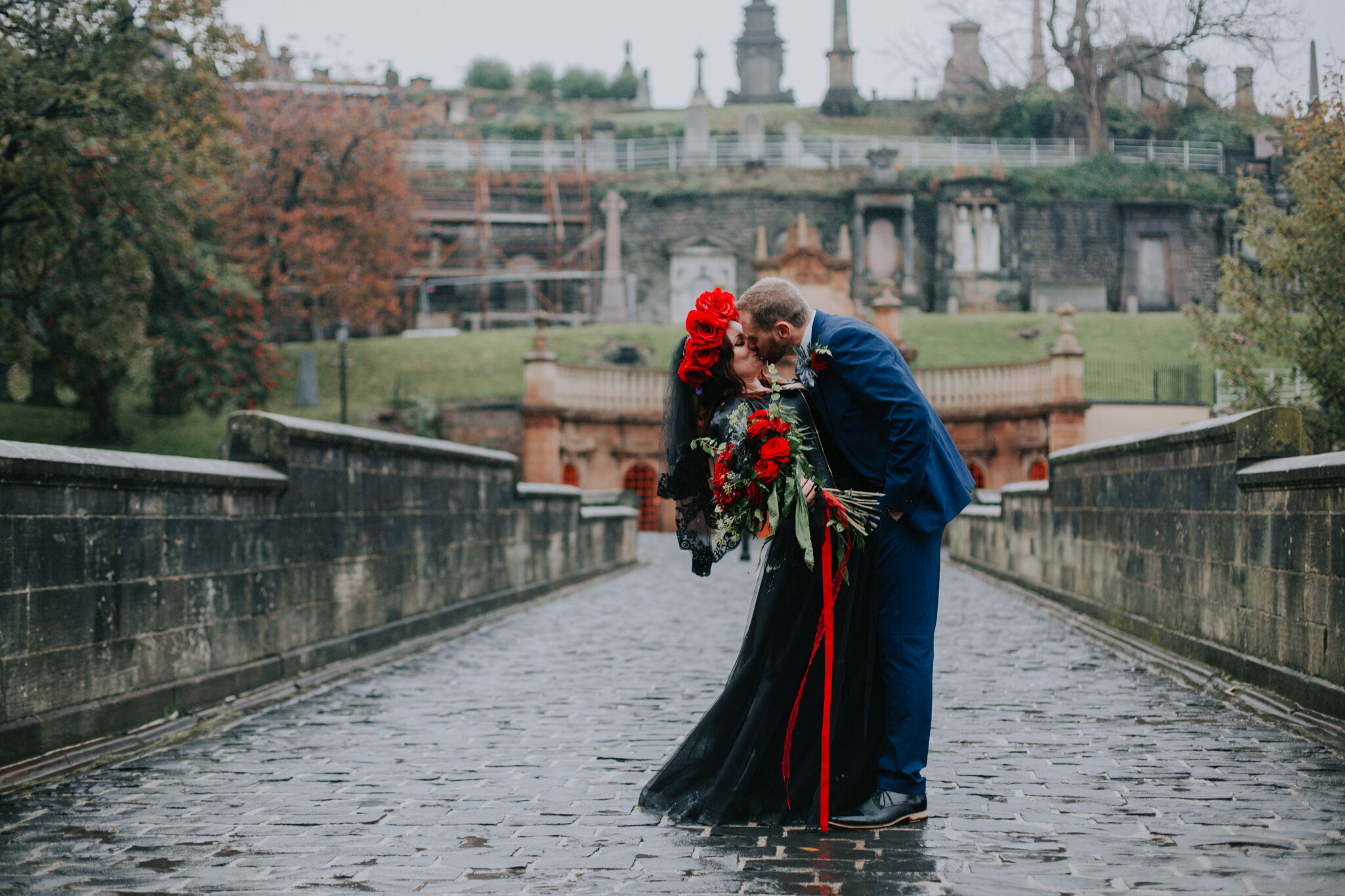 The couple is kissing on the bridge of the Glasgow Cathedral