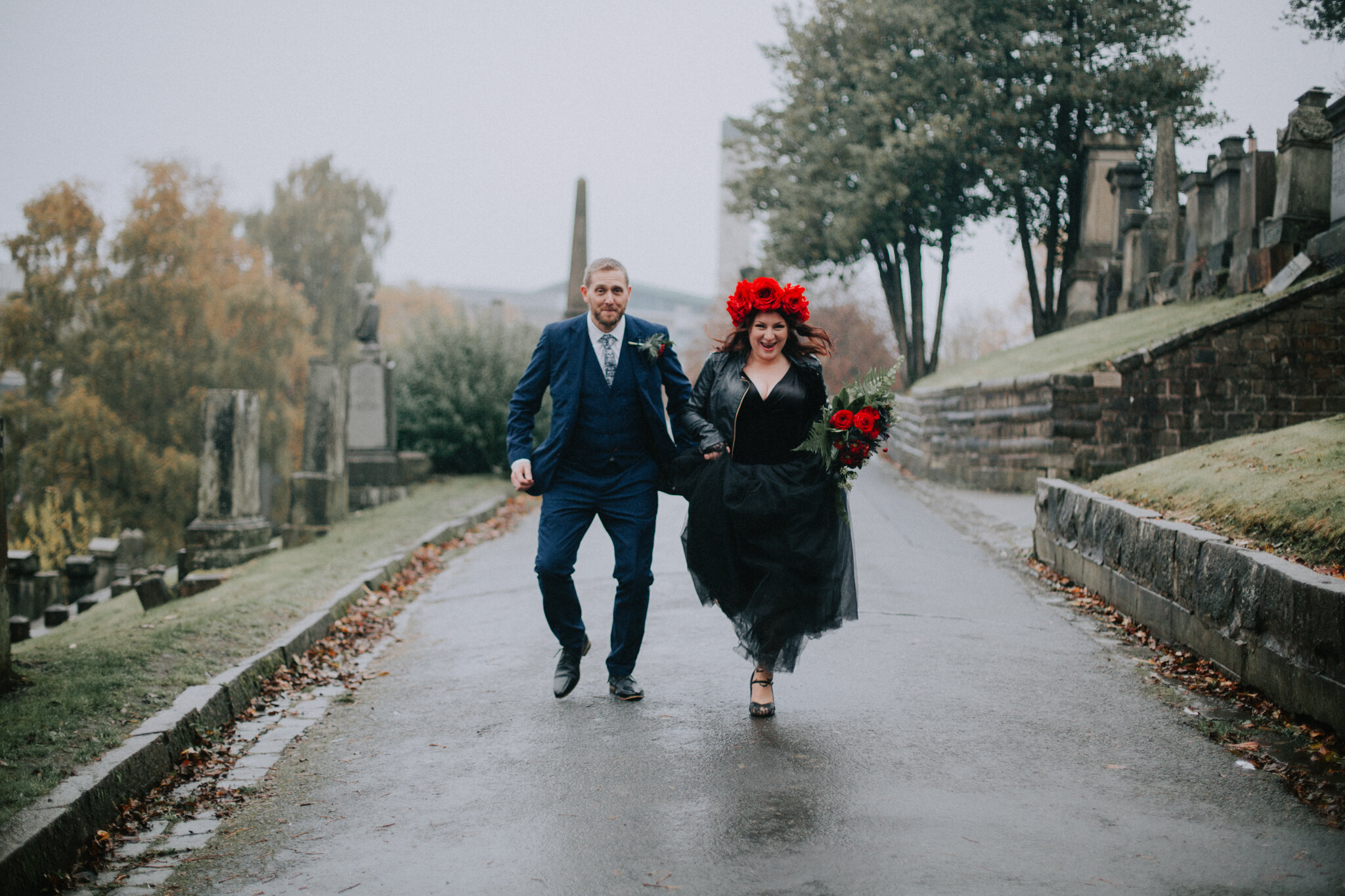 The couple is running at the Glasgow Cathedral graveyard