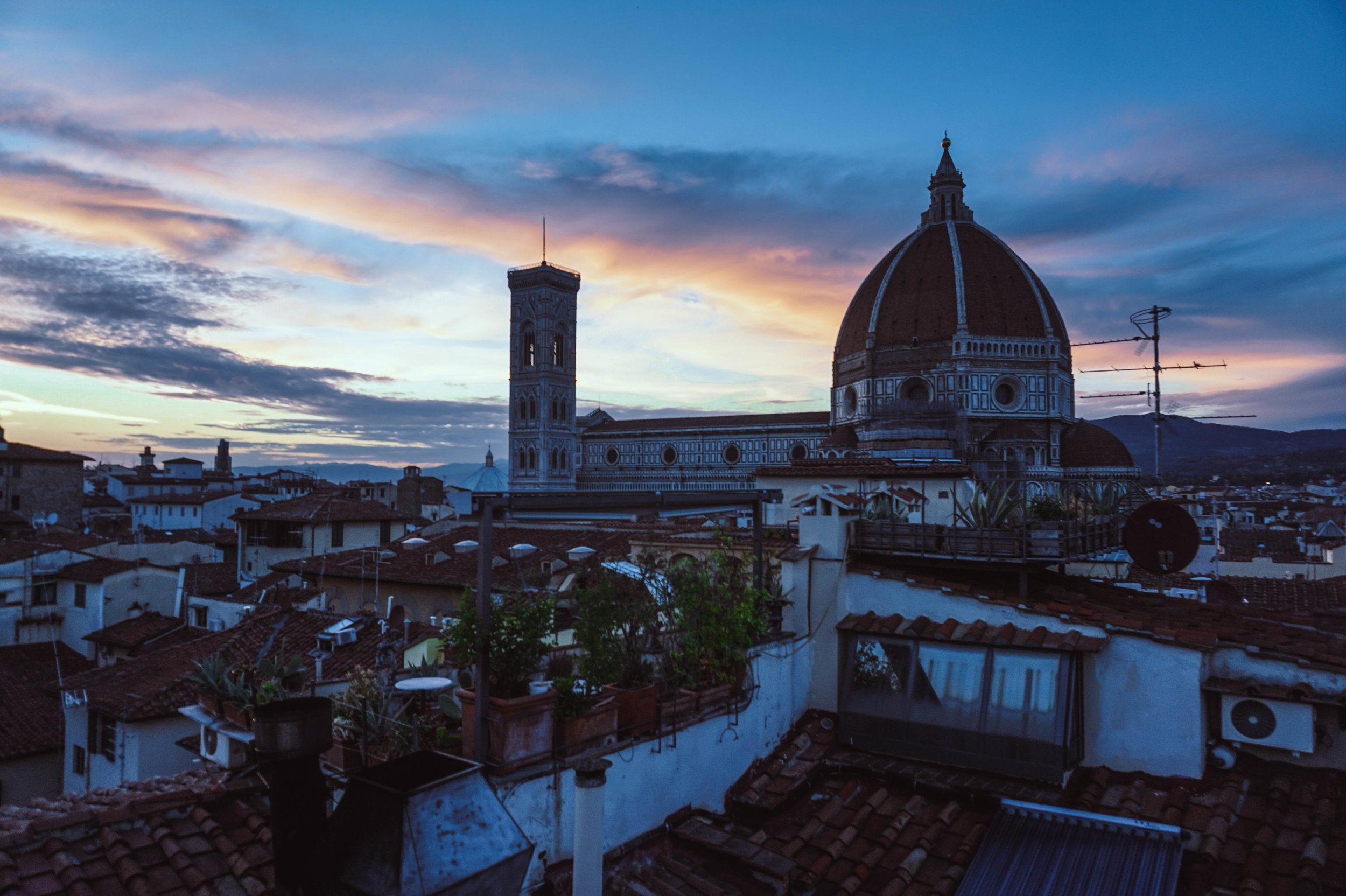 Rooftop view of the sunset behind Cattedrale di Santa Maria del Fiore