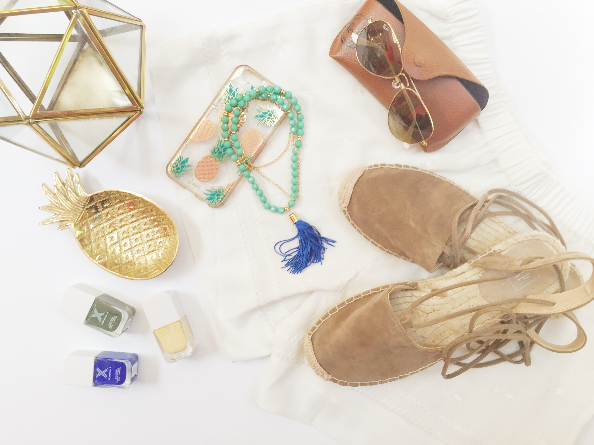 From top left to bottom right: (See bottom of post for a list of links to each item)Brass geo terrarium, pineapple phone case, beaded tassel necklace, aviators, pineapple trinket, nail varnish, embroidered shorts, lace up espadrilles.