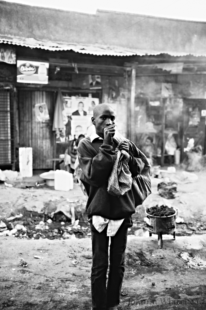 a young man stands just outside his home in the slum.
