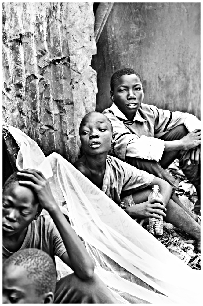 Boys from the slum sit and watch time pass while inhaling glue