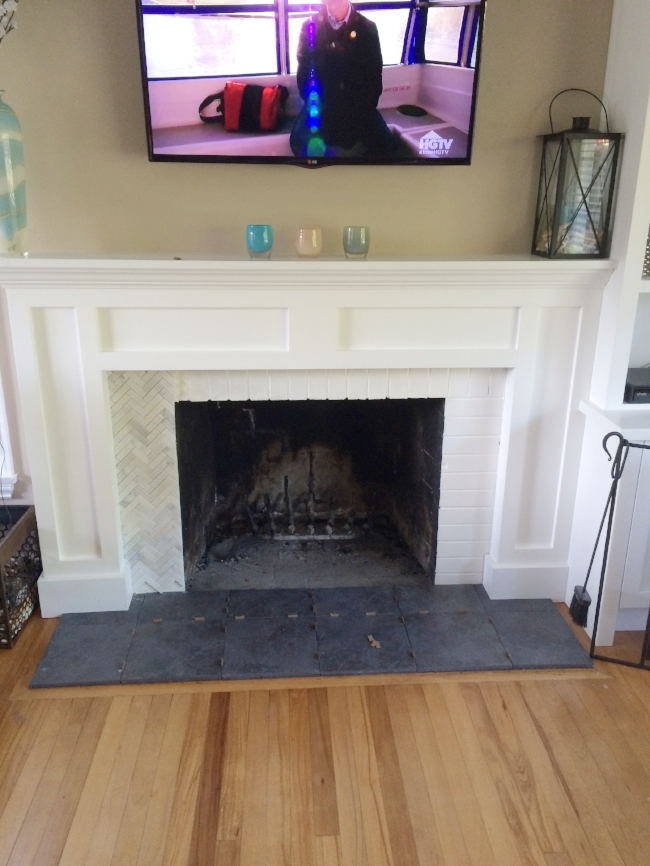 We replaced the brick surround with a herringbone tile and slate grey floor tile from  Lowe's .
