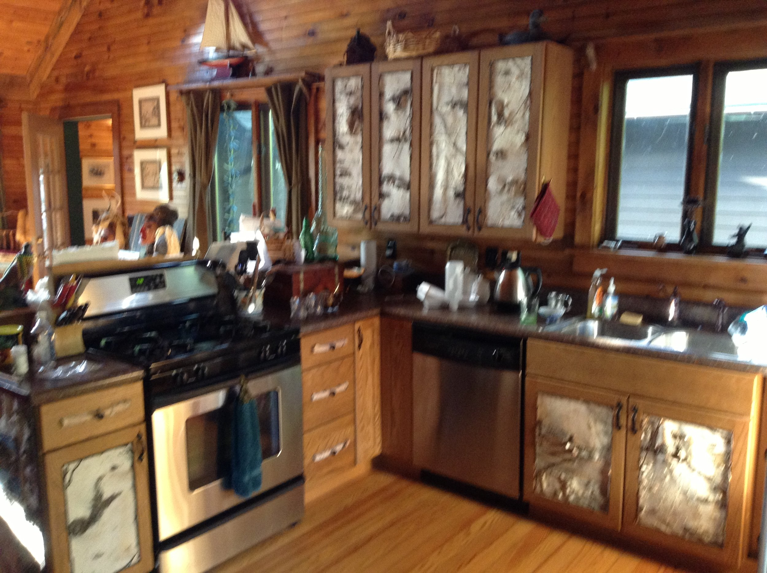 Kitchen cabinets with birch bark paneling and twig accents done by Anne